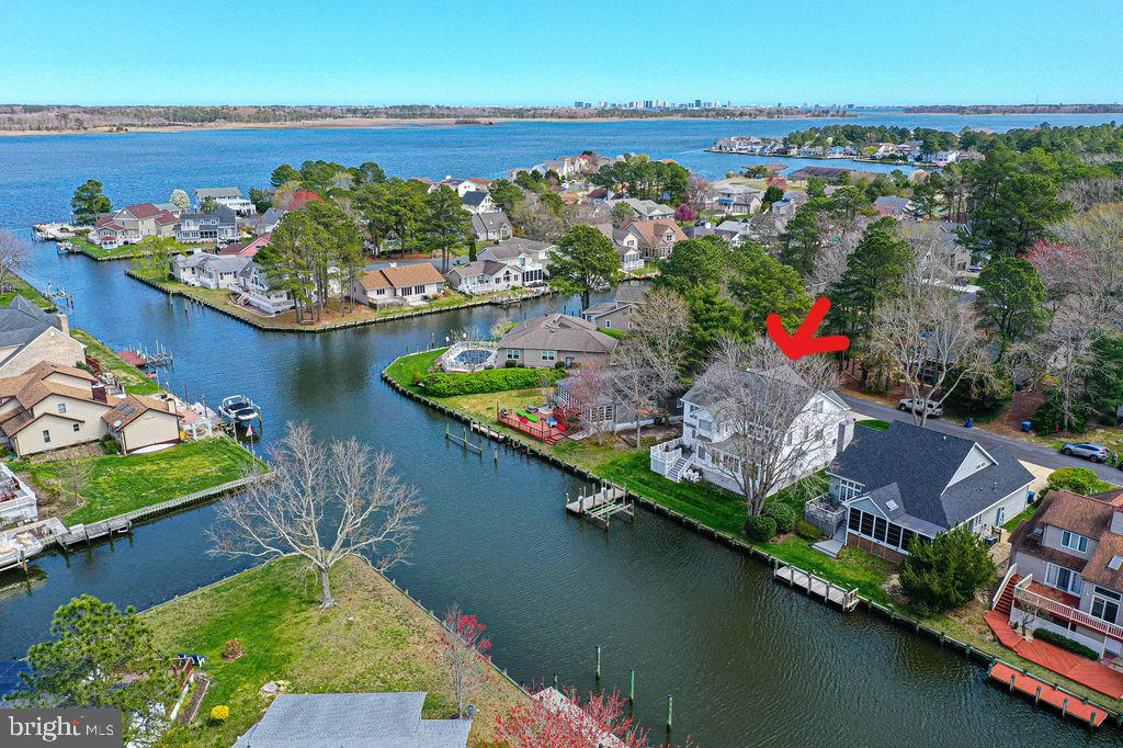 Waterfront elegance at its finest is available for your immediate enjoyment! This extraordinary Coastal Designed 4,000 sq. foot 5 bedroom 3 1/2 bath home with upscale furniture  Negotiable and is  Move In Ready! You are greeted by an open floor plan with Beautiful Water Views from every angle of home. Exceptional features of the home include a large inviting Foyer, Formal Dining Room; Great Room with custom built-in cabinetry and a  granite surround  gas fireplace. Enjoy an enchanting Sunroom with new carpet and French doors for privacy is perfect for your morning coffee or evening cocktail. This open and airy floor plan boasts a gourmet kitchen with granite counters stainless steel appliances upgraded cabinetry with tile floors throughout. Off the kitchen is  a large breakfast room with computer desk as well as  Wet Bar & Solarium  with slider doors that exit out to oversize trek deck with automatic sun setter awning.  Walk just steps to your 10,000 lb. boatlift as well as a dock that can easily accommodate two guest boats. Expansive second floor primary suite boast water views, cathedral ceilings newer carpet ceiling fan and walk in closet. Relax in your jetted whirlpool tub overlooking the serene water with automatic window treatments or enjoy large custom designed tile shower. Second bedroom overlooks the water with a private entrance to 2nd full bath; impressive third bedroom with separate office and sizable 4th bedroom located across from 3rd full bath. Family and guests will enjoy the 5th bedroom on 3rd floor suite with its own HVAC compressor and 3rd floor air handler keeps the 3rd floor as cool/warm as you want year-round. 3 floor suite could be utilized as an entertainment room, workout room, or guest bedroom. Home is complete with crown molding, dual sound system throughout all 3 floors, whole house Aprilaire 800 humidifier and main HVAC Compressor installed 2 years ago; wireless thermostats, heated and aired oversized two car garage, ample storage outdoo