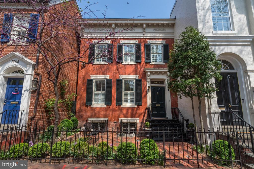 Located on a prominent street in Georgetown's East Village, this spectacular Federal semi-detached residence was originally constructed circa 1811. The beautiful brick façade is enhanced with elegant cornice moldings and embellished with splendid architectural details. There is a charming gated front garden, providing wonderful privacy. The house has been beautifully updated with extensive renovations and expansion, while still maintaining its significant historical elements. It features generously proportioned rooms that are great for formal entertaining, while maintaining a warmth and intimacy for comfortable family living. The residence captures an abundance of natural light from four different exposures. A gracious entry foyer leads to the sophisticated formal living room, which has lovely built-in bookshelves and a gas fireplace. The neighboring dining room with pocket doors features an additional fireplace and built-ins. There is a  renovated family room and open gourmet kitchen, which offers a large center island with breakfast bar and storage, high-end stainless-steel appliances, and custom cabinetry, including a large built-out pantry. The kitchen provides convenient access to the rear terrace, gardens, and two-car garage through a glass paneled exterior door. There is the added convenience of a nearby powder room. The second level landing leads to a large center hall, complemented with an exposed brick wall and oversized skylight. The impressive primary suite captures southern sunlight and has built-ins and a lovely gas fireplace with brick surround. The exceptional primary dressing room offers two walk-in closets and an additional gas fireplace. There is a beautifully renovated spa-inspired marble bathroom with dual vanities, a frameless glass shower with multiple shower heads, and a separate soaking tub.  There are two additional bedrooms on this floor that share an adjoining bathroom. The laundry room is also well located on this level. The spectacular 