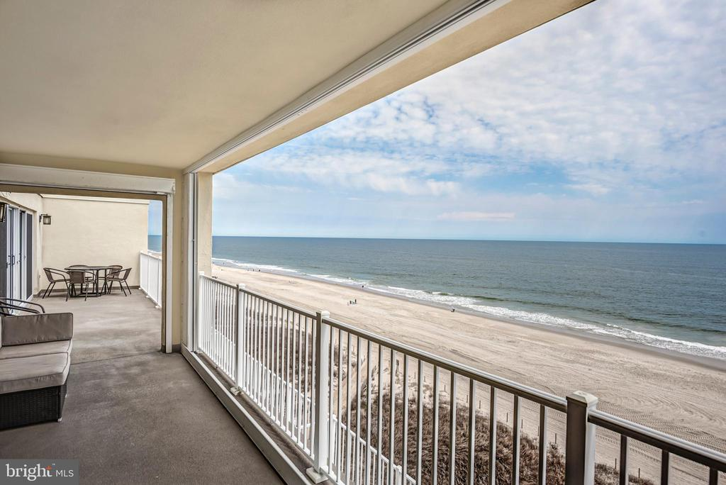 VIEWS!! Huge oceanfront 4 bedroom, 3 bath penthouse condo with one of the largest balconies in town. Condo has been recently renovated with beautiful wood coretec floors throughout, brand new coastal kitchen, and all new vanities in bathrooms. The large private 60 foot oceanfront balcony spans over the double wide living room and two front bedrooms. In addition to the main living room, there is a second living room/den with incredible views of the bay. Condo building is conveniently located walking distance to many amazing shops and restaurants. Parking, pool, security, and owner storage locker on site. Being sold fully furnished with all decor.