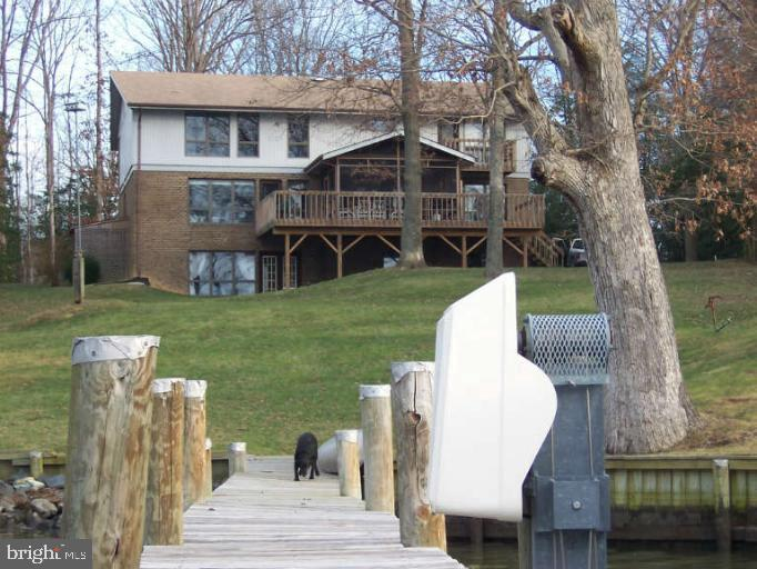 ***  WATER FRONT HOME ON 2 BEAUTIFUL ACRES ***  125 FT  DOCK W ITH BOAT LIFT*** WATER IS APPROXIMATELY 4 TO 5 FEET  DEEP AT THE END OF DOCK *** MASTER BEDROOM HAS A  BALCONY OVERLOOKING THE WATER AND LARGE SITTING ROOM WITH A WOOD STOVE ***  4th BEDROOM ON MAIN level  ***  FAMILY ROOM HAS A LARGE CONVERSATION PIT ***ALMOST EVERY ROOM IN HOME HAS A  MAGNIFICENT  VIEW OF THE DOCK AND WATER ***  FINISH THE 1700 Sq FT  WALKOUT LEVEL BASEMENT ,HAS A LARGE  FIREPLACE AND ROUGHT - IN FOR A FULL BATH *** WITH  THE FINISHED BASEMENT  THE HOME WILL BE APPROXIMATELY 5000 Sq FT *** LOCATED  ON PROTECTED WATER ABOUT 5 MINUTES TO THE POTOMAC RIVER *** LARGE DECK AND SCREEN PORCH FOR YOUR OUTDOOR ENTERTAINMENT ***