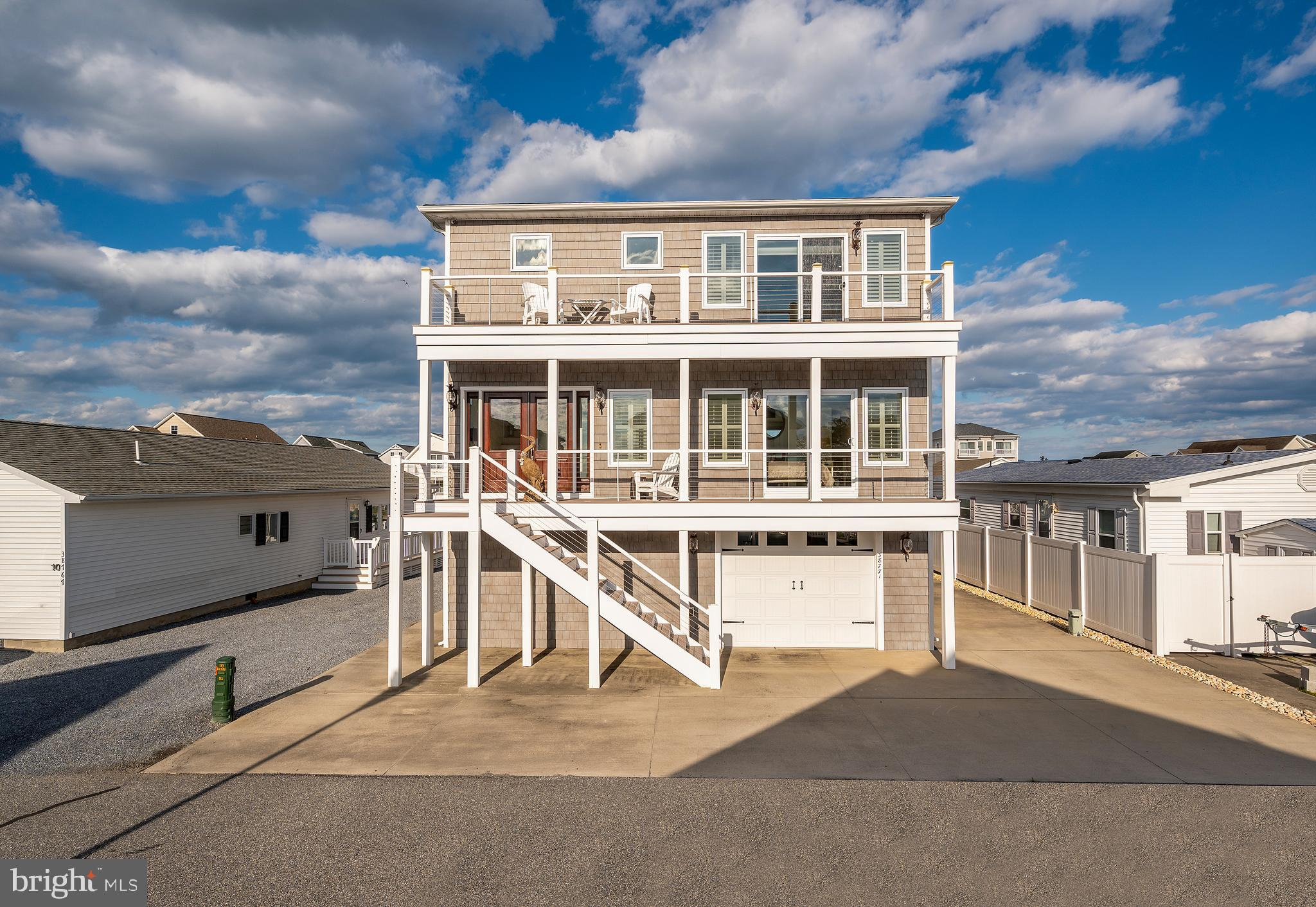 """When only the best will do… Amazing 4 bedroom, 4.5 bath home with your very own deep water boat slip right outside your back door.  From here you are just minutes to all the fun in the sun! This meticulously kept home is all you could want and more!  Featuring amazing water views from every angle, along with views of the Ocean City skyline. The main living area features an inviting open space that encompasses the family, kitchen, and dining area. Open the large sliders and let the outside in from the large waterfront deck.  Enjoy dining al fresco as the sun goes down and shimmers off the water! Cooking will be a joy in the Gourmet kitchen featuring high-end appliances including a  48"""" subzero refrigerator and a wolf professional range with double oven.  High end cabinetry, granite counter tops, and panoramic windows will make cooking a joy! Four generously sized en-suite bedrooms can accommodate all your friends and family comfortably.  Custom tiled showers and spacious baths make you feel like you are in a high end resort.  Three of the four bedrooms feature their own private decks. Love to work out? Spend a little time in the waterfront fitness room to get your beach body ready! You will love the oversized garage that not only has room for cars but all the beach and boating toys as well. No detail was overlooked, from the high end Hinkley pineapple exterior lights, plantation shutters, security system, elevator, whole house generator, owned solar panels, private dock with a boat lift, sea doo lift, an outside mister for those hot days, and more!  This maintenance free home, in the highly sought after waterfront community of Cape Windsor,  is ready for your enjoyment."""