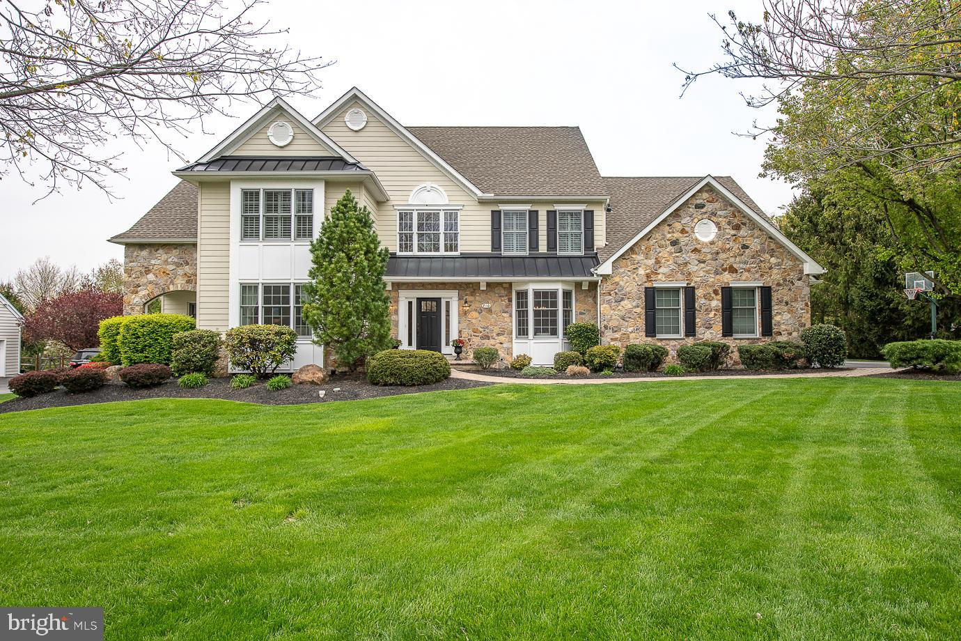 """Gorgeous classic stone home situated on a premium, private lot in the sought after community of """"Clocktower Woods"""" in East Goshen. No more stucco! Complete exterior renovation featuring Hardie-board siding, raised seam accent roofs on front elevation & over 3-car garage, new front & rear entry doors, new soffits & fascia, new TimberTech deck off Master Sitting Room & 3 new carriage style garage doors. Neutrally decorated & beautifully appointed with over 4,500 sq ft on 1st & 2nd floors featuring 5 Bedrooms, 4 full Baths, 1 half Bath, 4 FPs plus an add'l 1,500 sq ft of living space in the professionally finished Lower Level. 1st Floor features hardwood throughout, elegant 2-story Foyer w/turned staircase; Dining Rm w/hardwood, crown molding, wainscoting & window seat;  Living Rm w/hardwood, crown, triple window & gas FP; private Study w/glass doors, hardwood & custom built-ins; Family Room w/hardwood, crown, stone woodburning FP & exit to screened porch; Kitchen/Breakfast Rm w/hardwood, granite countertops, GE Cafe stainless 5-burner gas cooking & microwave, stainless French door refrig & Butler's Pantry; large vaulted Great Room/Sunroom addition w/gas FP, hardwood & casement windows w/transoms above; expanded Laundry/Mudroom w/custom lockers. 2nd floor offers luxury Master Suite w/hardwood, tray ceiling, triple window, 2 walk-in closets. Master Sitting Room exiting to private TimberTech deck & Master Bath w/enlarged tile stall shower, jetted soaking tub, skylites & granite top vanities; Princess Suite offers hardwood & private en-suite bath with tub/shower; 3 add'l family Bedrooms plus renovated Hall Bath w/subway tile shower & seamless doors. Finished Lower Level w/outside entry features 1,500 sq ft of living space incl Media Room & Game Room area, Bar area w/granite & wet bar, Professional Gym, gas FP plus Full Bath w/stall shower. Additional amenities include 3-car garage, new roof (2014), new HVAC (2017), plantation shutters throughout 2nd floor, designer custom"""