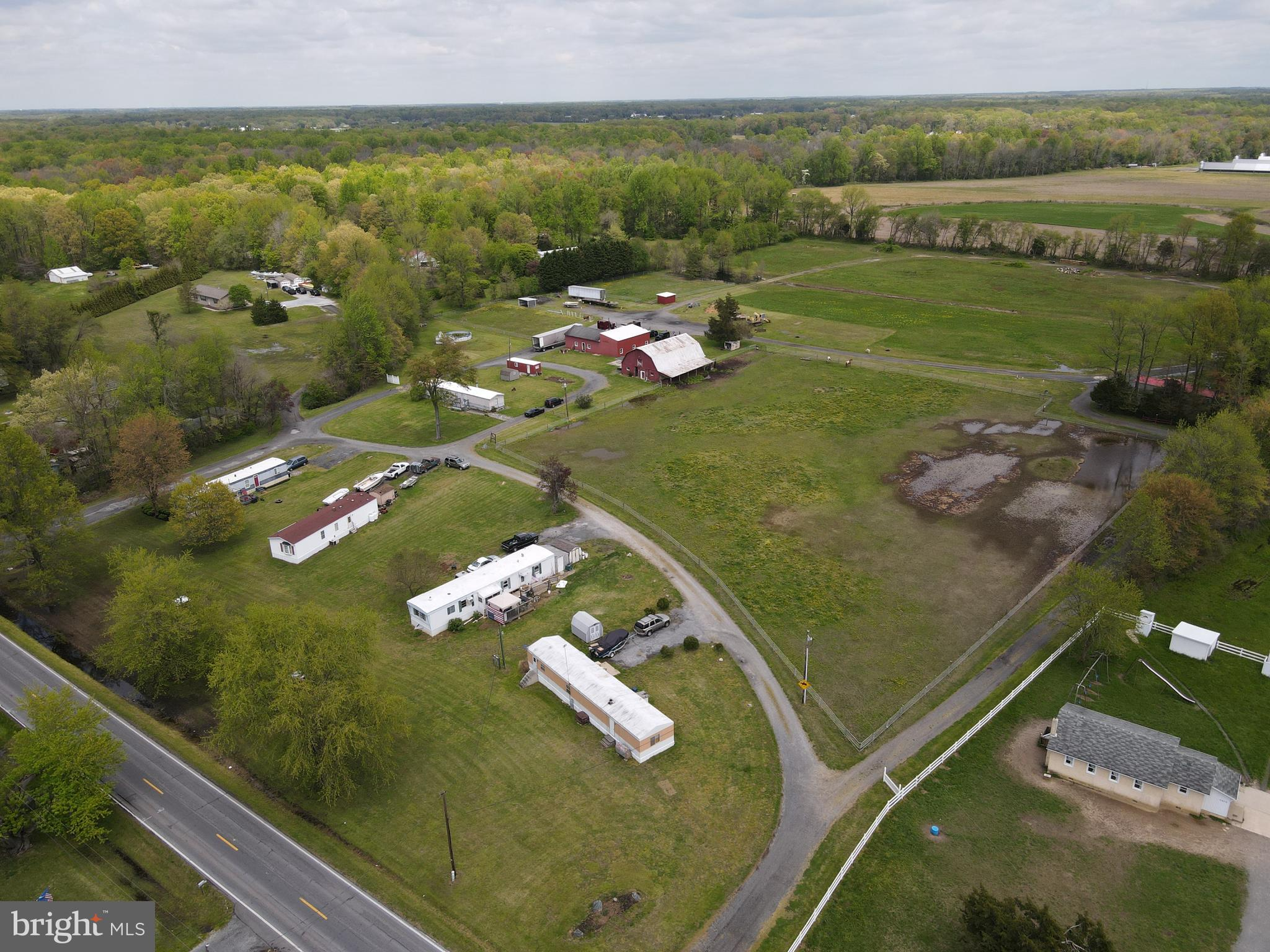 There are tons of possibilities and potential on this income producing farm listing.  Est 400 ft of road frontage with three already subdivided lots! Two 1/2 acres and one  3/4 acre  with septic and electric  already in place. All of this in addition to the 13.8 acre farm -  you don't want to miss out on this! There are two ponds perfect for fishing. There are six tenants already in place for $3500 monthly in land leased rentals. There are 6 septics and 2 deep wells. This farm comes with 1.4 acre of FLOATING (BN)commercial property! (Floating means it can be zoned business anywhere on the farm). You will find a list of potential approved businesses in disclosures. Perfect horse farm with 8 stalls in a  35x50  barn and three pastures, two run in sheds and a lean to off of the barn.The back fields are used for growing/baling hay. Currently there is a 18 wheeler/dump  trucking business  with  a 35x40  work shop on the property. This work shop has 2  large doors for pulling in vehicles/dump trucks on  concrete floors and electric throughout the building.   The main dwelling is currently tenant occupied  but has  retired trailer paperwork on permanent foundation.  Come see this unique and beautiful property! Co list agent is related to seller.((Watch the Video Tour above))