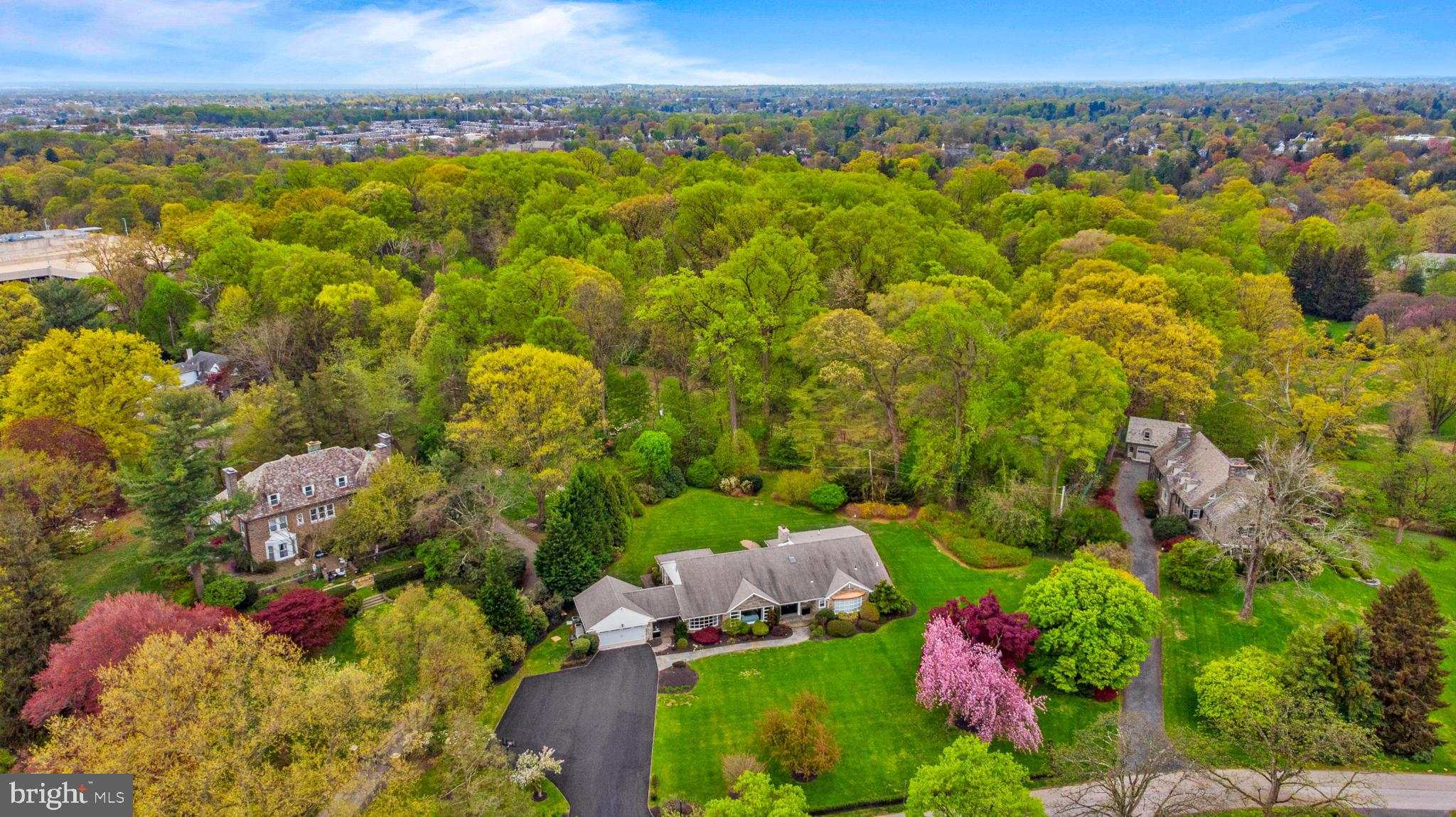 Sunday, 5/2, OPEN HOUSE CANCELLED.   Do you want the best house with the best yard in the best location?  Look no further.   Completely renovated between 2017 – 2021, no expense was spared to optimize the style and function of this beautiful stone Cape Cod home.  Ideally situated on over 1.17 acres of park-like land with private access to the Lankenau walking trail, this property offers  privacy within a neighborhood that is walkable to shopping, places of worship and commuter rail.  Step through the front door and into the entry foyer and you will notice that the beauty of the grounds  is brought indoors through many large windows and doorways.   High ceilings and hardwood floors throughout the house highlight the large spaces and open floorplan.   From the foyer with coat closet and powder room, step into the dramatic Great Room with stacked stone fireplace, barreled ceiling and wall of windows.  Pella sliding doors lead to a stone patio and back yard.   This room opens to a lavish gourmet kitchen featuring Italian Carrera Bianco marble countertops and island as well as custom designed, soft-close cabinetry and pantry.  A  Sub-Zero refrigerator/freezer, Sub-Zero beverage refrigerator, Wolf 6-burner gas range with commercial-grade Wolf vent/hood, Wolf microwave, Bosch stainless steel dishwasher and two stainless steel sinks make this kitchen both a showplace and a serious workspace.    The kitchen also has an informal dining area with door to the patio-- perfect for everyday meals.  Off the kitchen is a convenient laundry room with front loading washer and dryer.  The formal Dining Room is large enough to accommodate holiday gatherings and opens up to the formal Living Room; both rooms offer sweeping views of the front lawn from windows that nearly span the entire wall.  On the other side of the entry foyer are three generously sized bedrooms.  The  Primary Bedroom offers French doors to the back patio, his and hers walk-in closets and luxurious bath with oversized