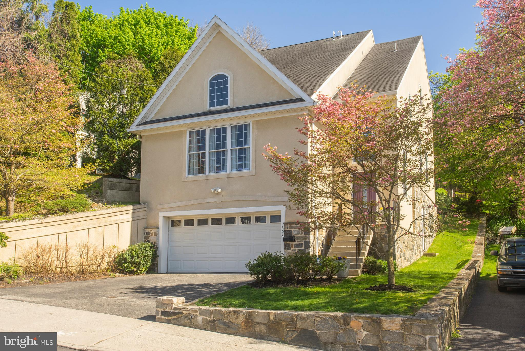 """Of all the neighborhoods in the Lower Merion School District, it's hard to find an easier commute and quicker access to I-76 than Bala Cynwyd's iconic Belmont Hills neighborhood. Built in 2003, this 2546 sq ft, 3 bed/2.2 bath single-family home can actually be considered """"newer"""" construction by local Main Line standards.   This contemporary Colonial-style home also boasts a parking abundance that's rare for the neighborhood, with a wide private driveway and an oversized two-car garage.   Once you're inside, you'll be struck by the dramatic, high-ceilinged entrance hall, freshly painted walls, and beautiful hardwood floors. The large eat-in kitchen features a gas range, double sink, and large peninsula with seating. The eating area overlooks a light-filled living room with cathedral ceilings and a fireplace. Also on the first floor is a powder room, a den/office, and a roomy family room with a pass-through to the kitchen and access to the paver patio out back.  Upstairs is the main bedroom suite, with a large walk-in closet and en suite with double sinks and walk-in shower. The second floor has two additional bedrooms, a full hall bath, and a laundry closet with a full-sized washer and dryer.   One of the home's key features is the huge flexible space in the walkout lower level. With its wet bar, powder room and storage area, this additional living space has potential as entertainment space, a playroom, or media room. As it has a separate entrance and some privacy from the rest of the home, this ground-level space could easily be converted to a fourth bedroom, or an in-law, guest, or au pair suite.  Other highlights include: Central AC, an ADT security system, pulldown attic access, hardwood floors and freshly painted walls through much of the house.  Note:  Three new interior doors have been ordered, to be installed after May 17"""