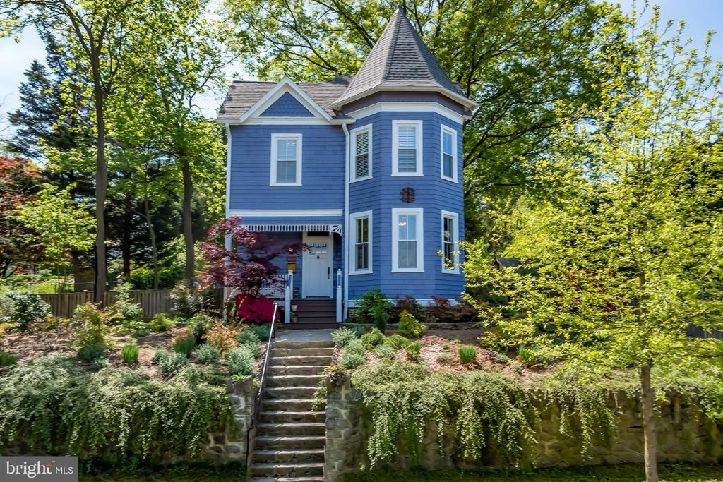 This house has a story to tell.  Could it be your story as well?   Nestled in Brookland, this expansive property--including the stately main house, detached 2-car garage with fully finished unit above, and inviting carriage house complete with stone fireplace--is a true treasure.   Featuring nearly 4000 sq ft of interior space including 5 bedrooms + office and 3.5 baths, the home is situated on nearly a quarter acre of picturesque land.  With azaleas in bloom and abundant grass underfoot, only the chirping birds will disrupt this sanctuary that sits in the shadow of a Franciscan monastery and convent.     A canopy of mature, stately trees shade the generous stone patio, with dappled sunlight peaking through, creating an idyllic outdoor space that extends directly from the stunning light-filled kitchen, resulting in a seamless flow from interior to exterior.  The main floor is rounded out with a living and dining room, and cherry hardwood floors throughout.   The second floor features a primary bedroom with en suite bathroom and separate sitting area, three additional bedrooms and a full hall bath--providing an ideal layout for a family.  The third floor is a pitched roof loft, suitable for a playroom, study or guest room.  The unfinished basement and an additional shed attached to the garage provide abundant storage options.   A concrete driveway is situated on the side of the house with an automatic gate providing secure off-street parking for 4-5 cars including 2 covered.  Newly installed French drain adjacent.   Homes like this one don't come along every day.  A captivating escape; an inviting retreat.  This is a house with a story to tell.   Make that story your own.