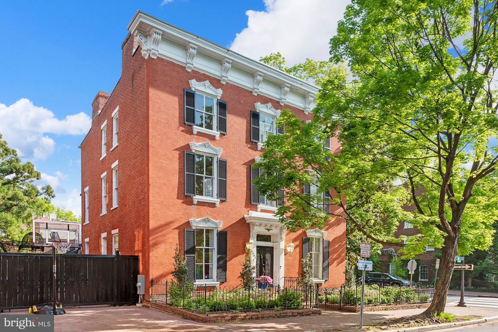 An archetype of Georgetown style, this stunning detached brick Federal exudes grace and sophistication. Sited prominently on one of Georgetown's most historic streets, this extraordinary home offers tremendous scale and grand proportions. Original details, high ceilings and light from a multitude of windows can be found throughout the home. The entry level enjoys light from four exposures and features a double living room, formal dining room, family room, powder room and a generous newly renovated eat-in kitchen with a wall of windows overlooking the expansive patio. The first upper level is home to a spacious primary bedroom with en-suite bathroom, a hall bath and two additional bedrooms that provide great flexibility as potential office or workout spaces. The top level has a hall bathroom and four very well proportioned bedrooms that enjoy abundant light. The lower level has a large family room, full bathroom and designated office space. Two car parking tops off the long list of amenities in this wonderful and significant home.
