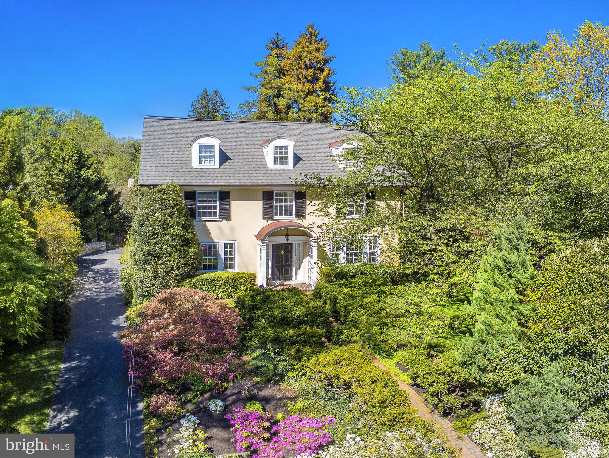 """Built in 1920, this classic 7 BR 4 Bath home in Lower Merion is both charming and inviting.  Nestled on a hill on a quiet street with specimen plantings, peace and tranquility pervade. The front hallway opens to living room featuring an intricately carved fireplace with emerald surround mantle. Abundant sunlight fills the glass window """"sleeping porch"""" with access to rear patio, reminiscent of miniature Longwood Gardens! At the end of the center hall is a powder room. To the left is the gracious sunlit dining room, leading to the kitchen . Pass through the Butler's Pantry with built ins, conveniently located next to kitchen with Dual Fuel Wolf oven and breakfast area. The laundry is adjacent with storage area and leads to 2 car garage with """"trap door"""" conversion for easy access. There is another garage and beyond a garden wall that separates garage from the lovely gardens. There is a small potting shed where the lilacs bloom and infuse the air with heavenly perfume! Inside ascend the stairs , on the left is  a guest room with double closet. The main bedroom is spacious with large windows admitting sunshine. The bath is updated and adjacent to a large closet. The third bedroom is adjacent to a full bath and linen closet. The 4th bedroom and closet is charming with a full bath and  separate storage closet with built ins. Additionally on the 3rd floor there is a full bath with claw foot tub, 5th/6th bedroom with closets. The 7th bedroom is perfect for au pair or guests, complete with cedar closet and attic access. The lower level has ample storage with two separate closets, and outside access. This home offers timeless beauty and is located in the top rated Lower Merion School District. It is literally within 8  minute walking distance to the Bryn Mawr train, Baldwin School, Bryn Mawr College and Shipley Schools. This home is a treasure and will be cherished by the new fortunate owners!"""