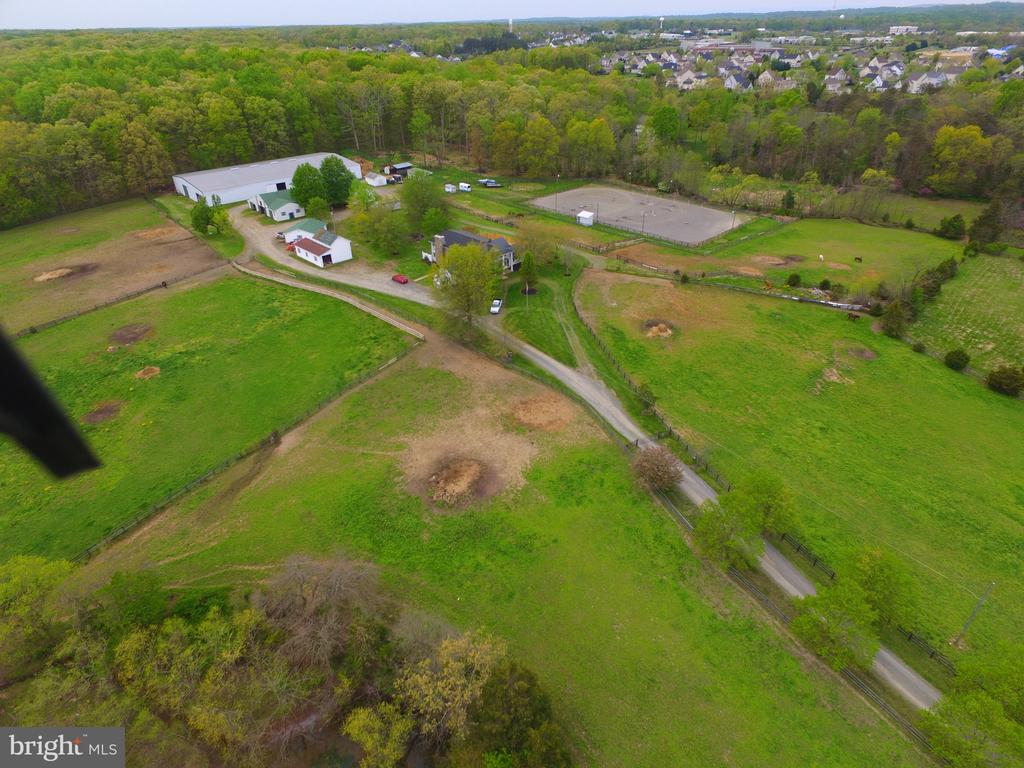 If your dream is to run your own EQUESTRIAN facility, here's your opportunity to do what you love and make money.   Included is a 27 stall barn with a one bedroom apartment, an additional 15 stalls in various sheds/barns,  a 122 X 175 indoor arena built in 2011,  a large outdoor arena, round pen, ample storage and numerous pastures with auto waterers. a gorgeous spring fed pond, 3 bay garage, a spacious 6 BR, 4 .5 BA home, a pool, koi pond, and a gated driveway make this a great property to run your equestrian business or simply use for personal enjoyment.    Sold strictly AS-IS.  Lovely setting and totally useable.  The property is situated on 27.8 acres, located in PW County, with approximately  2 AC located in Fauquier County.