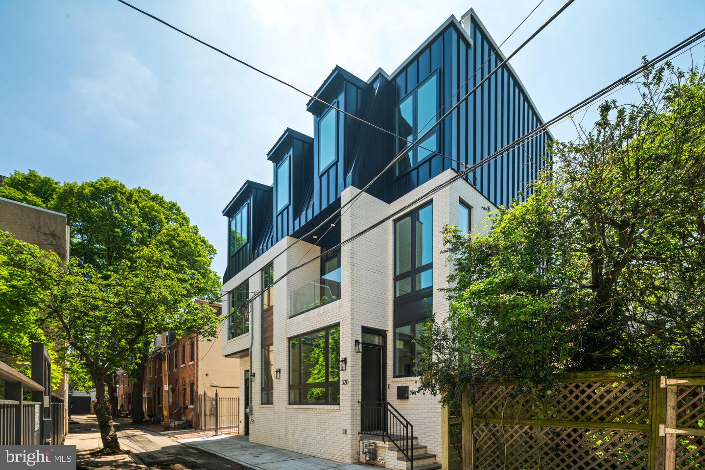 This unique, completely detached home, is unlike any you will find in the city.  Sitting on a 42 foot wide lot, this home is 39 feet wide.  Absolutely stunning from the inside out, located on a quiet, secluded street in the heart of Queen Village.  Almost 4,000 square feet of living space featuring a 2 car garage, 4 bedrooms, 4.5 bathrooms, Elevator, 3 outdoor spaces, Meredith Catchment, approved 10 year tax abatement, tons of closet space and much more. Upon entering you are welcomed by a large beautiful bright foyer, this first level also has the 2 car garage and large bedroom with full en-suite bath perfect for a guest room, office, workout space or den. Walk up to the sprawling, wide open main level with tall ceilings and flooded with natural light. This floor is complete with the timeless chef's kitchen featuring top of the line Miele and Sub-Zero appliances,  as well as high end  custom cabinetry and a stunning marble and mother of pearl backsplash.  The large dining room leads out to a balcony overlooking the quiet tree lined street. The living room is centered around a beautiful fireplace. This level also has a convenient powder room, huge walk-in pantry adjacent to the kitchen as well as an extremely convenient large laundry room. Up one more level to three bedrooms conveniently all on one floor.  Primary bedroom has a walk-in closet and jaw dropping en-bathroom, complete with soaking tub, 2 separate vanities and luxurious glass enclosed shower.   Up one more level is a large and very private roof deck with sprawling City views including the Center City Skyline and both Ben Franklin and Walt Whitman Bridges. The elevator is accessible on every level from the finished basement to the roof deck. The finished basement if very large with high ceilings, fantastic natural light and another full bathroom ideal for an extra hangout space, home gym or both. This luxurious home checks all the boxes and is ready for you to move in!  Move right in to this 100% complete