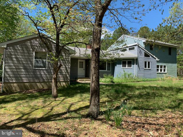 """Here's an opportunity to own a 2,527 square foot contemporary home on 4.87 acres with 5 bedrooms, 4.5 baths set back off of Route 563 in Woodland Township.  There are two (2) primary bedrooms w/their own bathrooms on the first floor.  Three (3) more bedrooms upstairs with a full bath.  The kitchen has unique windows allowing rays of sunlight, double ovens, abundant cabinets and counter space & lighted ceiling fan.  Take note of the specially designed """"cookie counter"""".   Eat-in kitchen space and a formal dining area with hardwood floors.  There's an option to name this bonus room as the office/den/kid space w/built-in shelving and a propane fireplace.  Right around the corner is the family room w/laminate flooring, the other side of the dual fireplace and sliding glass doors to the back porch with a propane stove and a hot tub (status unknown).  Solar hot water with electric back-up, backyard wired for an above ground pool, newer dishwasher, garbage disposal and washer/dryer.  Inside entrance from the two (2) car garage has adequate work space.   Upgraded HVAC system (oil), underground oil tank removed w/new tank in the garage, acid neutralizer for water system, oversized septic tank and fields, irrigation system covers all of lawn and gardens (zoned), whole house alarm,  interior recently painted, full basement includes playroom, craft room and office.  There are three (3) lots totaling 4.87 acres in an """"L"""" shape.  Needs TLC and Being sold in """"As Is"""" condition.   *Sign @ the property driveway*"""