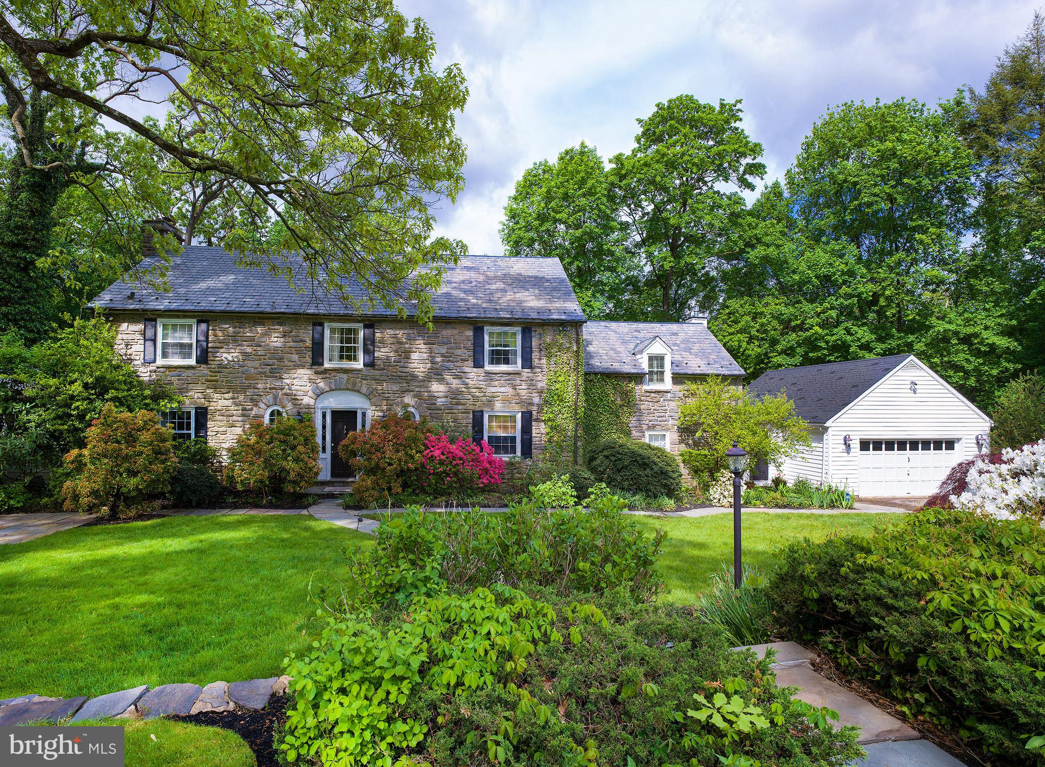 This gracious colonial in Bala Cynwyd welcomes your family home with a prime location on a private road on a quiet cul-de-sac of only eight residences. Its elegant exterior with slate roof makes a great first impression, while beautiful grounds and spacious patios provide a peaceful setting for outdoor enjoyment and entertaining. Inside is just as inviting, featuring generously-sized rooms, hardwood floors, large windows, glass French doors, and quality millwork.   Off the entry foyer sits a convenient powder room, handsome office for working remotely, and elegant living room with a wood-burning fireplace to gather around with loved ones or guests. From here you can read, relax and catch some rays in the enclosed sunroom enveloped by windows looking out at nature, or share formal meals together in the airy dining room with tasteful corner built-ins. Nearby is a light-filled open kitchen appointed with granite counters, a marble island with secondary sink, stainless steel appliances, and a sky-lit breakfast area for snacks and morning coffee.   A step-down open family room adjoins, offering a comfortable, relaxing setting with a gas fireplace and built-ins. Glass-paneled doors from both the kitchen and family room lead to the expansive rear patio for easy indoor-outdoor living. A large mudroom completes this level affording access to the front and back of the house, as well as the oversized 2-car garage.   Upstairs, a lovely landing with built-in sitting area greets you and proceeds to the sleeping quarters. The primary bedroom is the highlight of course, with a brand new deck, 2 walk-in closets, and en-suite bath with 2 sinks and refreshing rain head shower. An additional bedroom with walk-in closet, 2 more bedroom suites, and a laundry room with cedar closet also occupy the 2nd level. Topping the homes appeal is abundant closet space, a partially finished basement with powder room, central air, security system, and prime location in the award-winning Lower Merion S