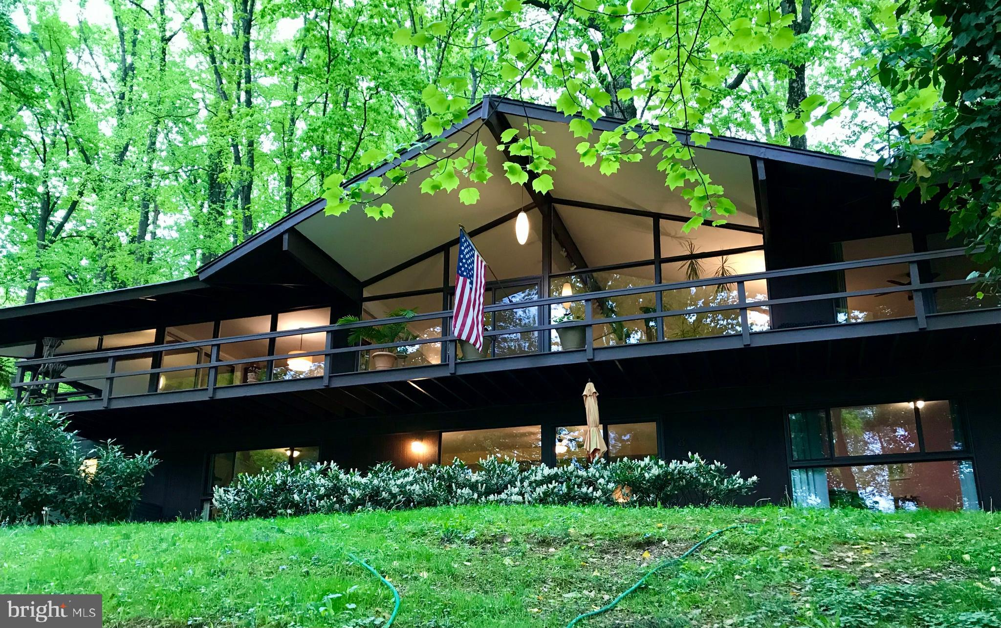 """Live in an architectural gem on a cul-de-sac in Wayne!  This stunning mid-century modern home was designed by renowned Philadelphia architect Robert McElroy, known for melding the natural surroundings into his airy floor plans. This unique home has great flow and is impressively sited on a wooded .71 acre lot. It has been meticulously restored and maintained by its current owner. Walls of glass in the living room, dining room, kitchen, family room and bedrooms render the home sundrenched and exceptionally bright, with the natural light playing on the home's interiors. The panoramic views in all directions make you feel as though you are living in a tree house! Vaulted ceiling with exposed beams in the living area with floor to ceiling glass on 3 sides, a free standing steel fireplace original to the home, expansive covered patio off of the kitchen and dining room sliders for total relaxation,  easy outdoor living  and  entertaining, and one of only 10 homes on the cul de sac. Award winning Tredyffrin-Easttown schools, low taxes,  and only minutes to the centers of Wayne and King of Prussia for shopping and dining. Convenient to Radnor train station and all major routes for commuting.   Main floor owner suite for one level living.  All hardwood floors on main living level and master bedroom has sliders to the deck. Three generously sized bedrooms on the lower level along with a family room/den/office/study, the second bathroom, an additional patio for more outdoor pleasure, and a mud room/laundry room leading to the 2 car attached garage.  Modern eat-in kitchen has 42"""" cabinets with undermount lighting, granite counters, stainless steel appliances (including built in microwave and French door refrigerator/freezer) and recessed lighting. Master bathroom boasts a large walk in shower, granite counters,  and double sink vanity. Second bathroom is also updated and has a tub with shower and large linen closet. Beautiful grounds, a wraparound deck that runs the length of t"""