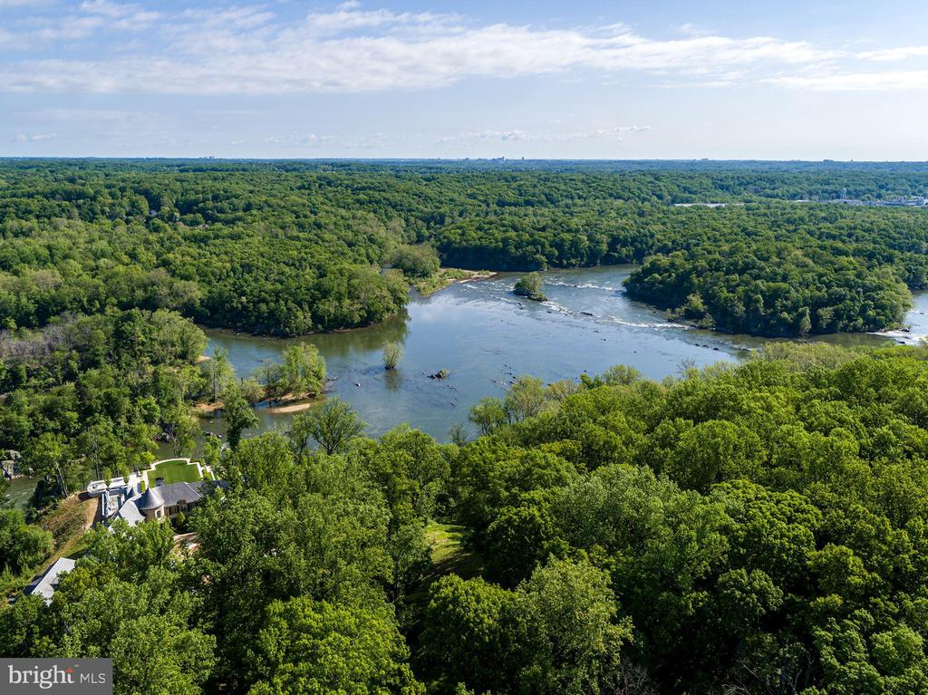 Privately nestled far off Georgetown Pike and directly on the banks of the Potomac River are the 5.17 acres that encompass 701 Bulls Neck Road. This property has spectacular sightlines and views ranging from the sweeping tree tops down to the flowing waters of the Potomac. The panoramic scene glides along the River and boasts utmost privacy with lush woodlands and neighboring parkland surrounding the home. There are 50+ acres of adjoining parkland that is a nature conservancy, adding to the idyllic quality of this amazing lot. 701 Bulls Neck Road encompasses a Mid-Century Modern home that spans nearly 2,400 SF and is comprised of 5 Bedrooms and 3.5 Baths. Perched atop the extensive grounds, the property is perfectly situated to showcase the picturesque views from nearly every room. This is an incredible opportunity to reimagine and rebuild your dream home along the Potomac River.