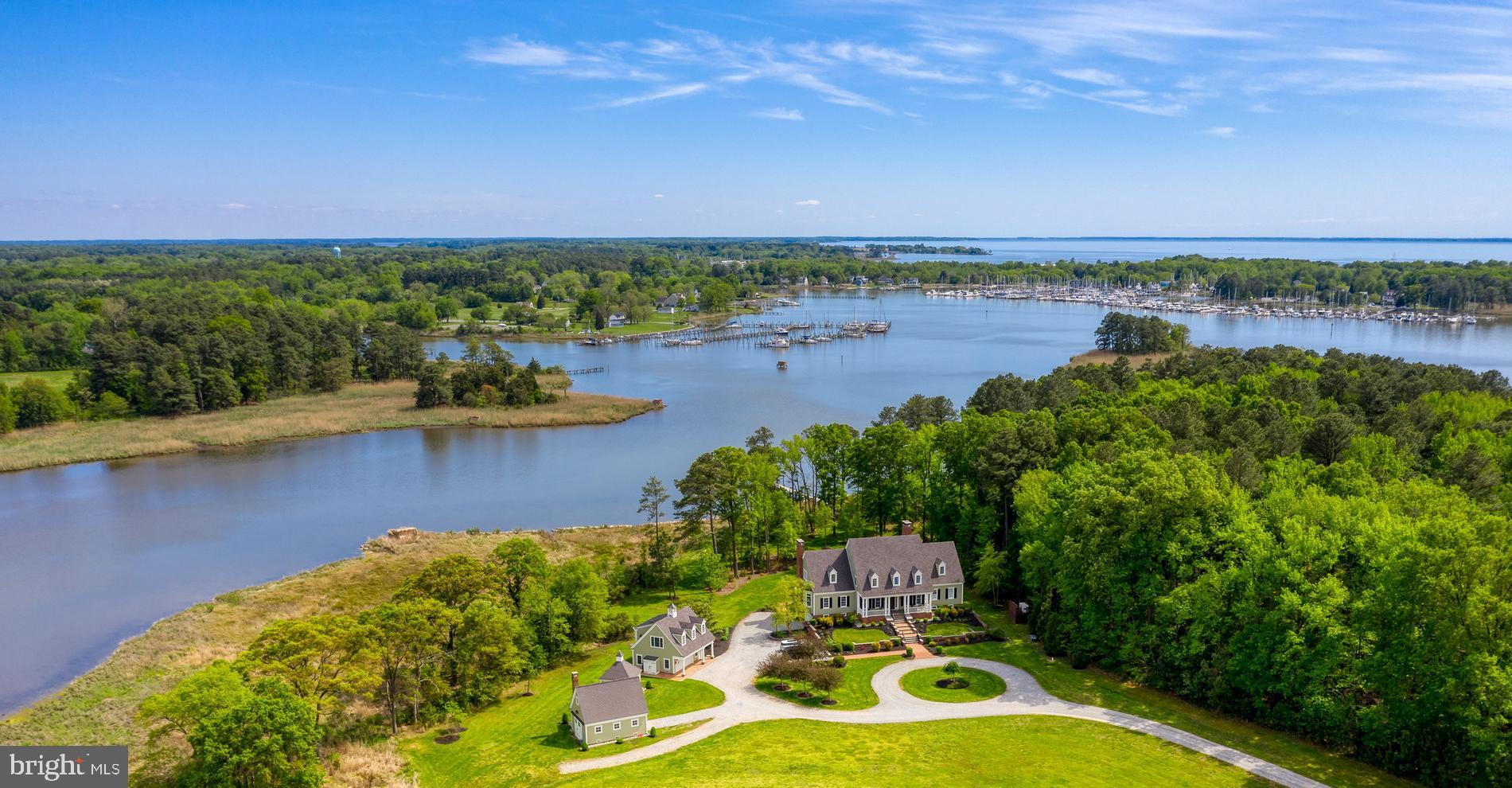 You will immediately notice the exceptional quality of design as you approach the circular drive and the majestic terraced entrance for this stately residence, which beautifully blends all the best features of a classic Eastern Shore lifestyle.  Comprised of two waterfront parcels, a total of 100 acres, providing an epic hunting location and/or simply a private natural setting with an abundunce of deer, ducks, herons, eagles, turkeys, fox and much more...  The home is situated on protected Swan Haven, and  has been constructed with meticulous attention to every detail.  With approximately 5,000 square feet, there is an easy open flow into the formal dining room, the gourmet kitchen with casual dining space, an elegant living room with a beautiful fireplace, and an expansive game room with the feel of a modern hunting lodge - bright and airy, yet with a nod to old-world tradition, complete with a wet bar and another breathtaking wood burning fireplace. The sumptuous primary bedroom and bath are also located on the first floor. The second floor has four bedrooms and three more full baths.  The main residence has a full basement and an attached garage and is surrounded by extensive landscaping, leading to a tranquil gunite pool.  A favorite spot is the brick patio area, designed with the same impeccable attention to detail,  with ample seating space and a large outdoor fireplace, perfect for entertaining by the pool or enjoying cool fall evenings.  Everything is oriented to the iconic waterfront views of Swan Creek, which affords easy access within just a few minutes to the mouth of the Chesapeake Bay, and is beautiful during any season, all year long.  Keep your boat at the private dock and enjoy an afternoon of crabbing or fishing, or enjoy a short ride on the creek, passing four marinas along the way to Rock Hall and the bay. There are four additional accessory buildings, including a garage with a guest apartment on the second level. All buildings were designed with