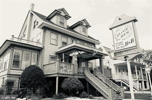 """The Atlantic House is one of the few remaining quaint 1920's Victorian Beach Houses in Ocean City, Maryland. Built prior to the 1933 hurricane, which created a new 50-foot wide, 8-foot deep """"Inlet"""" at the south end of town, Atlantic House has 13 rooms and is located one block north of Ocean City's """"City Hall"""", which was originally the elementary school. The decorative frieze boards and dentils at the dormer gables are classic Victorian elements. Other notable architectural features are the balustrades above the porches and a southern facing Sunroom in which you can enjoy our buffet breakfast. The symmetrical double hung windows and porches provide a perfect vantage point to watch the world pass by as you relax. Experience the charm of yesteryear at the Atlantic House, located in Old Town Ocean City. Features include: Relaxing Front Porch, Individually Decorated Rooms, Cable Television, Off Street Parking, 13 rooms with Private Baths  and Air Conditioning .  Atlantic House B&B is located just a half block to both the ocean and boardwalk, and a short walk to the bay for beautiful sunsets. Restaurants, clubs, and amusements abound all within walking distance."""