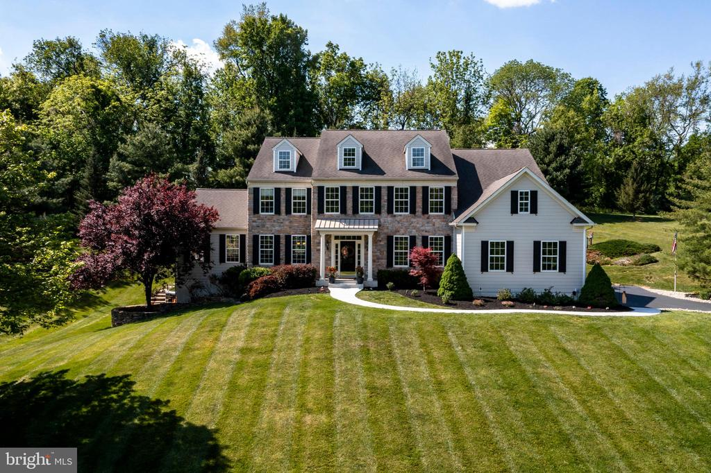 This MAGNIFICENT 5 Bedroom, 4.5 Bath Masterpiece with Conservatory is perched on a private 1.9 acre lot and set amongst a small enclave of homes.  Elegance abounds upon entering the grand, two-story marble Foyer with curved staircase and custom millwork and it continues into the Living and Dining Rooms, each showcasing exquisite wainscoting and crown molding detail with hardwood floors that flow seamlessly throughout the First Floor. French doors lead into the Conservatory, beautifully encased in three walls of windows and a vaulted ceiling that allows the natural light to flow in and create a serene   escape. This special area of the home is a perfect place for a home gym, playroom, music room or as a second office.  Prepare meals or prepare to entertain in the expansive gourmet Kitchen with sprawling counters, new backsplash, extensive custom cabinetry, gas cooking, double wall oven, walk-in pantry, huge granite center island with seating, and Dining Area that overlooks the private backyard and opens into the Family Room with stone fireplace, rear staircase and exit to the backyard. Laundry Room with plenty of cabinets and folding area, updated Powder Room, and Office with French doors complete the Main Floor. Outdoor entertaining is a delight on the secluded patio surrounded by rolling lawn, flowering shrubs, and trees. Into the evening, the overhead string lights create a festive atmosphere.  Back inside, both the turned staircase and rear stairs off the family room lead to the second floor where you will find the spacious Master Suite offering a Sitting Area, beautiful views of the backyard, vaulted ceiling, 2 walk-in closets, and Master Bathroom with vaulted ceiling, jetted tub, shower, and 2 separate vanities. A second Bedroom offers a Full en suite Bathroom, and two additional Bedrooms share a Jack and Jill Bathroom. Next to the fifth Bedroom is a bonus 12 x 6 walk-in closet that would be perfect for off-season clothing and extra storage. The Finished Walkou