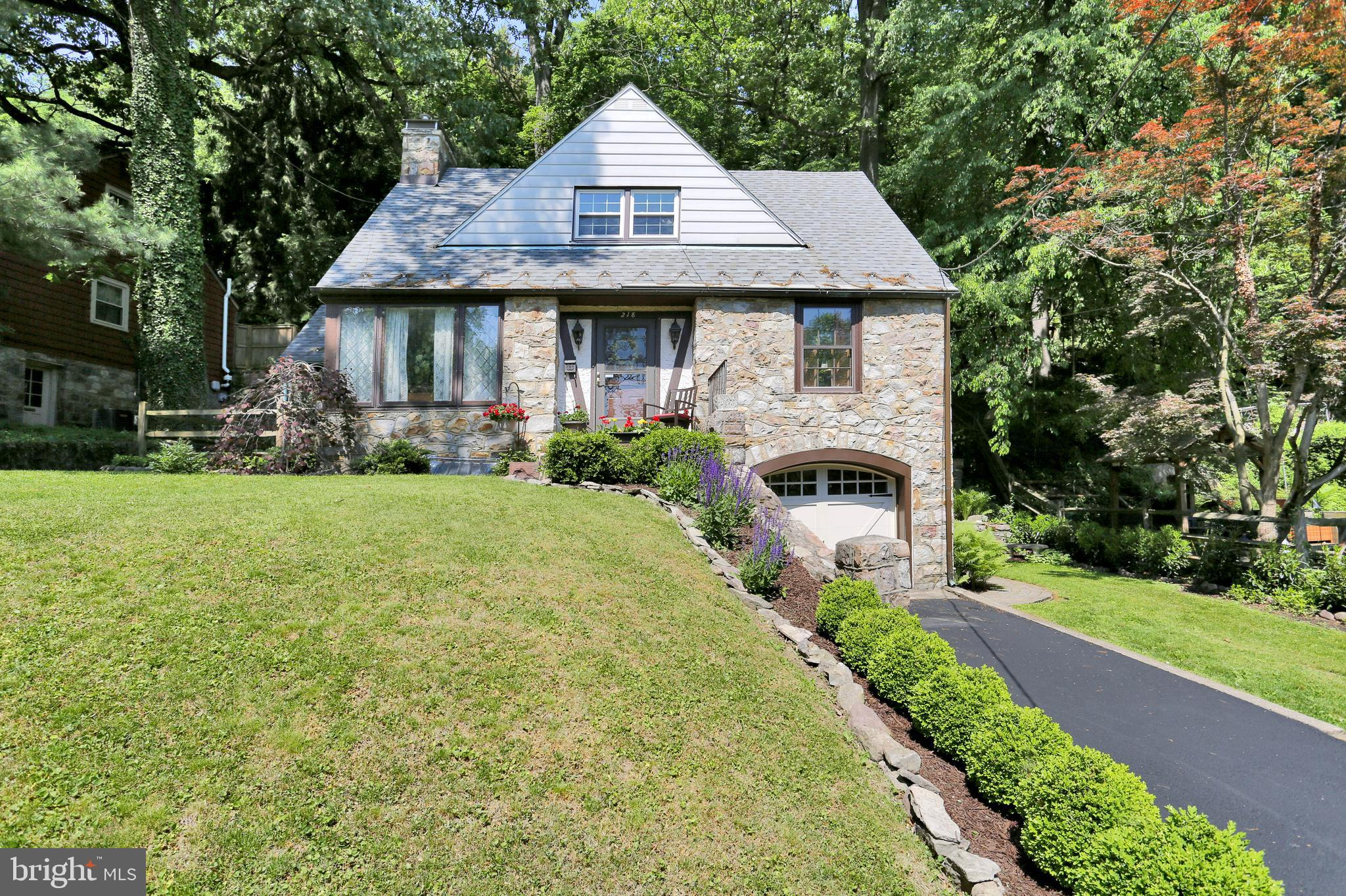 This Mt Penn Single boasts tons of charm inside and out!  Stone Tudor style  exterior has beautiful curb appeal along with mature landscaping!  Inviting living room space with stone fireplace the focus point of the room.  French style doors lead to side slated flagstone patio.  2nd floor features 2 bedrooms and possible 3rd (which is currently a huge walk in closet)! Remodeled full bath upstairs and a balcony with a view of the woods!  Possible 4th bedroom on 1st floor with another full bath!  Lovely dining room space leads to galley kitchen.  Full basement with lots of storage space, laundry, and 1 car garage.  All newer mechanicals including central air!  Rear of the home is all wooded with an original stone fireplace to sit and relax with friends!  There is also some grass turf that completes the backyard, easy to maintain!  Hurry up and take a look!