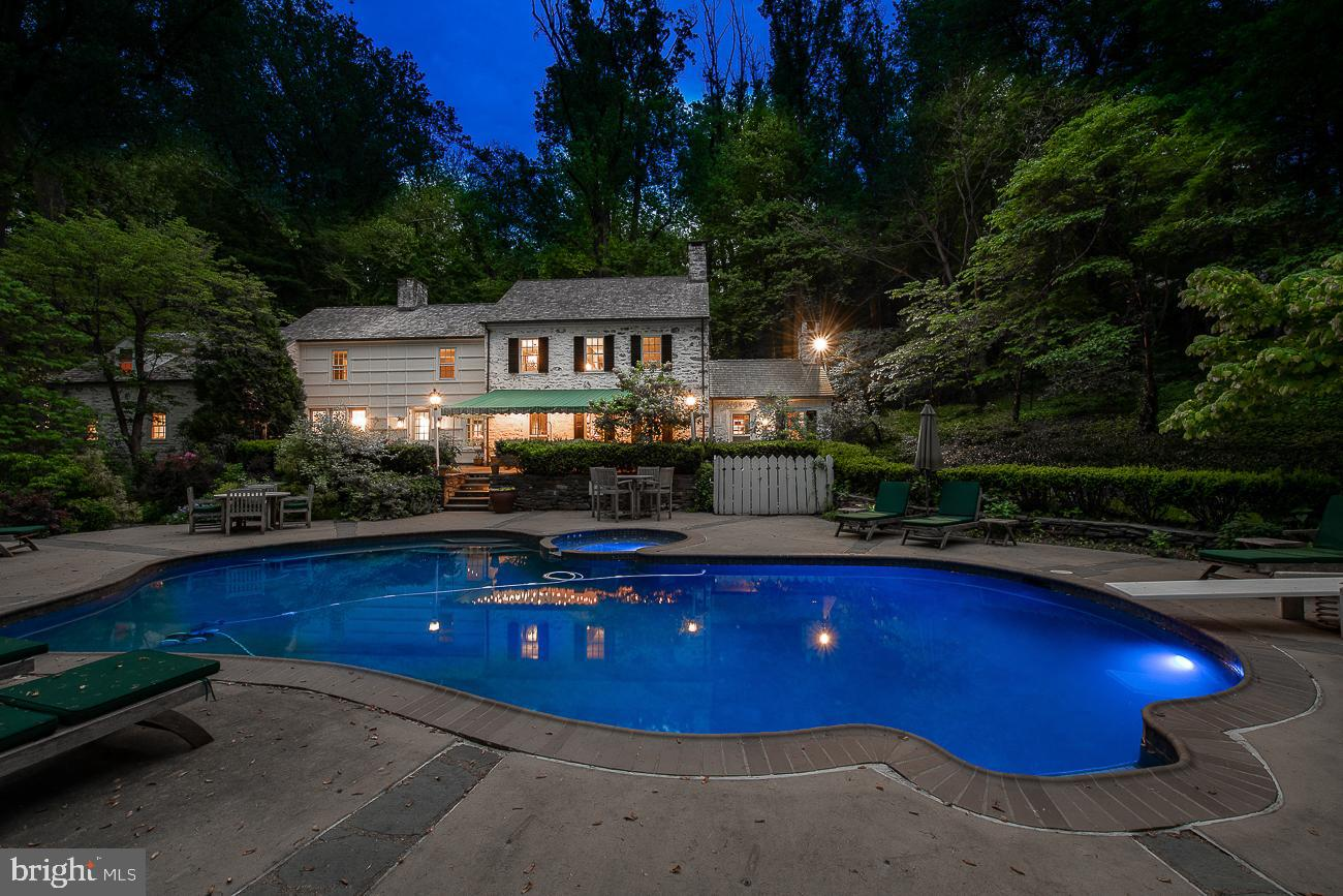 This truly classic Walter Durham Main Line colonial set upon 3.46 lush acres of privacy yet minutes to the Village of Gladwyne and downtown Ardmore exudes the classic Main Line lifestyle.  As you walk up the stone path and enter the front door you immediately see the views of the rear grounds with a beautiful pool and spa overlooking lush trees and personally designed English gardens. The formal living room with an abundance of built-in cabinetry and original moldings makes a wonderful room to entertain with its built-in bar discreetly tucked behind cabinetry and its classic stone fireplace. The spacious dining room is conveniently located off the kitchen through an arched doorway and features a grand fireplace surrounded by original built-ins and has a Dutch door leading out to the rear flagstone patio.  A cozy family room provides a wonderful place to spend time with family or can be used as a separate playroom.  The bright eat-in kitchen boasts Rutt cabinetry with granite counters, farmhouse sink, a new Bosch dishwasher, new Subzero refrigerator, and new wine cooler, double ovens, and gas cooktop plus back staircase.  The sliding door provides a plethora of light and makes access to the rear patio and pool convenient for grilling and outdoor entertaining. Tucked just off the mudroom in its own space, is the 4th bedroom and full bath perfect for guests plus a separate office/bonus space.  On the second level find the gracious primary suite surrounded by windows on three walls with a fireplace and offers views overlooking the rear grounds. The adjacent primary bath has a walk-in shower and concrete counters evoking a warm rustic farmhouse feel. Off the primary bath is a room currently being used as a closet surrounded by custom enclosed cabinets but could also be used as a 5th bedroom/office/bonus space.  The second floor also houses Bedrooms 2 & 3 which are also bright and spacious and offer adequate closet space and their own baths. A walk-up third floor is unfin