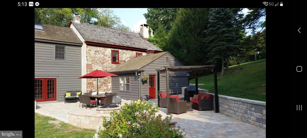 Boyertown area Farmhouse circa 1750.  Enjoy the charming character of the deep window sills, old floor, a walk in fireplace along with the modern updates.    This delightful stone and cedar clapboard farmhouse has a cedar shake roof replaced in 2008, 2 car garages with storage and a potential man cave.  Relax on the beautiful paver patio with retaining wall  and enjoy the built in fire pit and  the view of the creek across the street.  There also is 4-6 car driveway parking.   Walk into the gorgeous kitchen with hand made cabinetry from Dutch Built Kitchens,  tile floor, double porcelain sink, prep sink, a movable island, open beams, window seat with storage two pantries and a coat closet.   Entertain in the dining room with the gorgeous walk in fireplace with wood mantle, built in bookcase, deep window sills  and stone wall.  The living room has wood beams, a programable NEST thermostat,  deep window sills. There is a family room/office with built in shelves, wood beams,  full bath and a staircase leading to the primary bedroom.  2nd floor has full bath with ceramic tile, pedestal sink, tub/shower and 2 closets and a built in.  Primary bedroom with skylight, oversized double closet and ceiling fan.  Two additional bedrooms with closets, deep window sills, one has a working fireplace.  Basement is clean, newer water softener, new well tank, newer hot water heater, newer propane boiler, UV light and filter, laundry and Bilco door access.