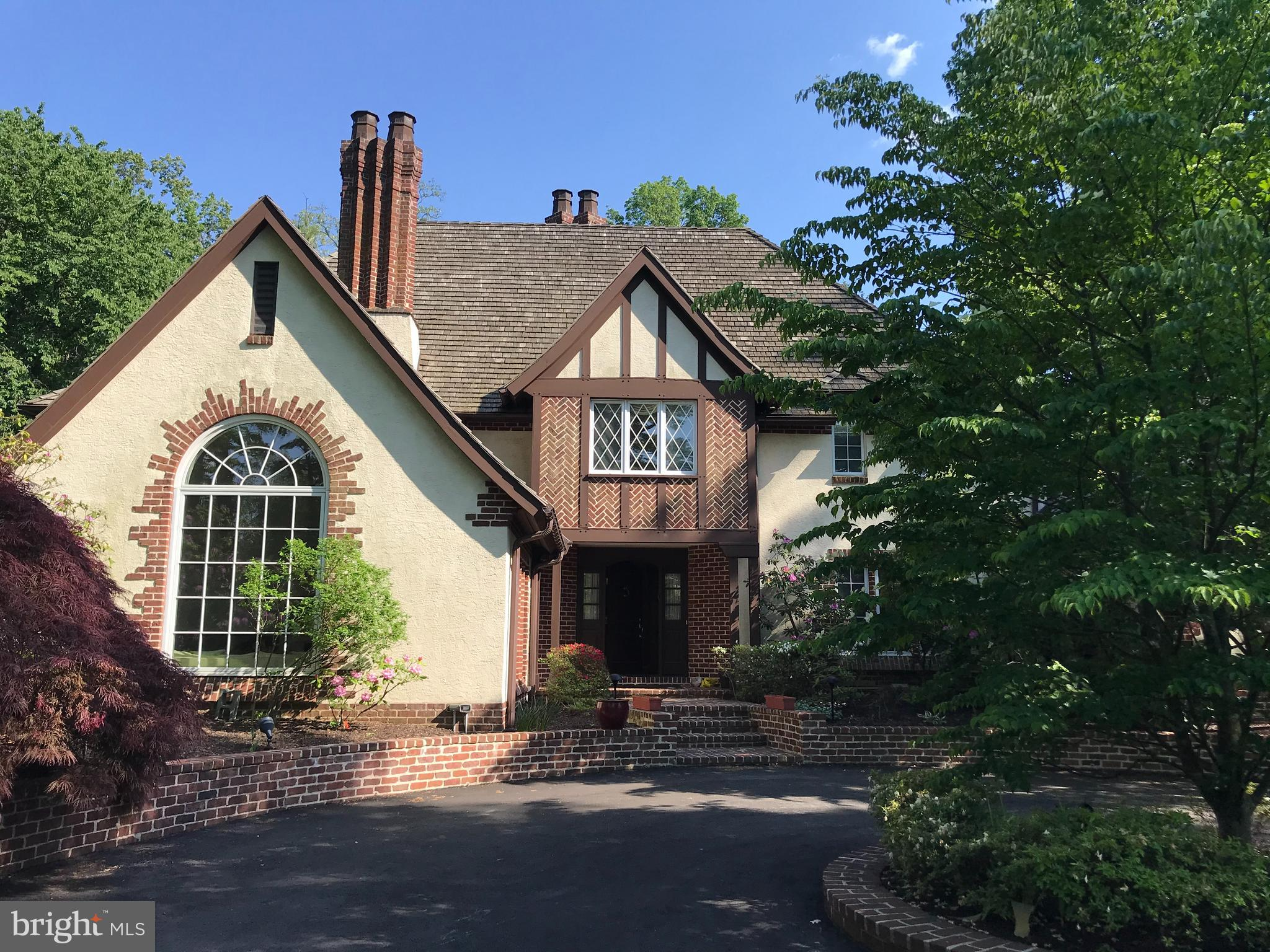 """Welcome to the """"One of a Kind"""" Custom Tudor Home in Prestigious Villanova.  This wonderful home is situated on a picturesque 1.33 acre lot offering an abundance of privacy and exquisite landscaping.  The exterior of this elegant home features a circular driveway and beautiful architectural details.  This """"One of a Kind"""" home has a rear patio with awning that is very inviting and creates a sense of Tranquility. This property has been meticulously maintained inside and outside. 705 Cedar Lane offers 4 bedrooms and 3 ½ baths. Exquisite craftsmanship throughout with detailed moldings and millwork.  2 Fireplaces, Beautiful pegged hardwood Floors and also a much sought after bedroom suite on the main level.  The Bedroom Suite on the Main Level features a large Bathroom and generous closet Spaces. On the Second Level you will find a Large Main Bedroom suite with abundant closet spaces and lovely Au-suite bathroom.  Two other bedrooms on this level with a Jack and Jill Bathroom. Highlights include: a large family room with Fireplace (gas insert) Cathedral Ceiling with Trusses and Built-in wet bar.  A Gourmet Kitchen  that would delight any chef with it's Custom Cabinetry, Granite Countertops, Sub-zero refrigerator and separate full size Sub-zero Freezer; Bosch 5 burner gas range, along with 2 Bosh wall ovens and Bosh dishwasher, Microwave and Wine Cooler. The kitchen also features a Center Island and a generous Breakfast room area with French Doors that lead out to the inviting patio which is perfect for dining """"Al Fresco"""". The Living Room features 15 ft. ceilings, large Palladium window and wood burning fireplace. Large Formal Dining Room perfect for Holiday Festivities. Powder Room on this Main Level.  The flow to the Floor Plan and The magnificent outdoor spaces make this home a perfect place for entertaining and active Living.  The lower level is finished and perfect for an At Home Gym or Recreation Room.  Large full Attic with easy access staircase and over-sized cedar"""