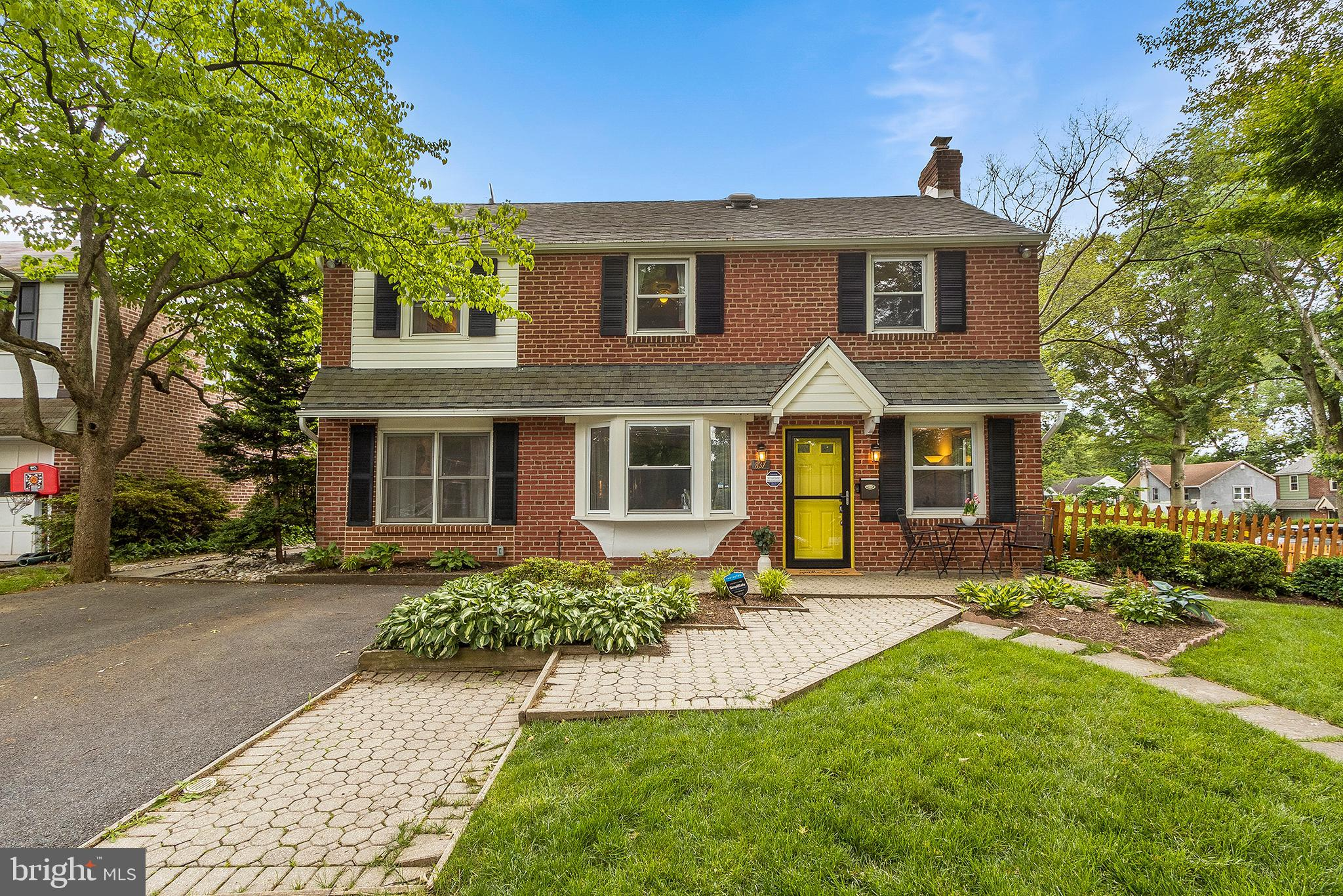This traditional brick colonial home is ideally located on a fenced corner property with exceptionally deep side and back yards. The updated interior and open concept design offers spacious living on three finished levels. The main level is transitional and features continuous hardwood flooring throughout. The front entrance opens into a casual Living Room and is highlighted by the smartly outfitted Chef's Kitchen and large open Dining area with a deep bay window and painted white brick fireplace.  The spacious and bright Family Room features built-in bookcases and storage at the side entrance with access to the raised brick terrace and deck opening to the flat rear yard privatized by evergreens.  This room is the ideal everything space, great for studying, television or entertaining.  Ascend a turned staircase to the Owners Suite featuring truly superior space and styling. Vaulted ceilings, an exquisite bath completed in 2020 with a spacious spa- like shower, wash-stand height vanities, terrific light, and complimented by a large walk-in closet. Three additional guest bedrooms, which also offer ideal home office space, recently updated bath with double sinks, a laundry area and storage complete this level. The lower level was recently renovated and provides a combination of recreation, work, and gym space, craft sink, and more storage.  Perfectly located on the lower part of the mainline, with all of its conveniences including easy access to the city, Whole Foods and Lower Merion Schools.