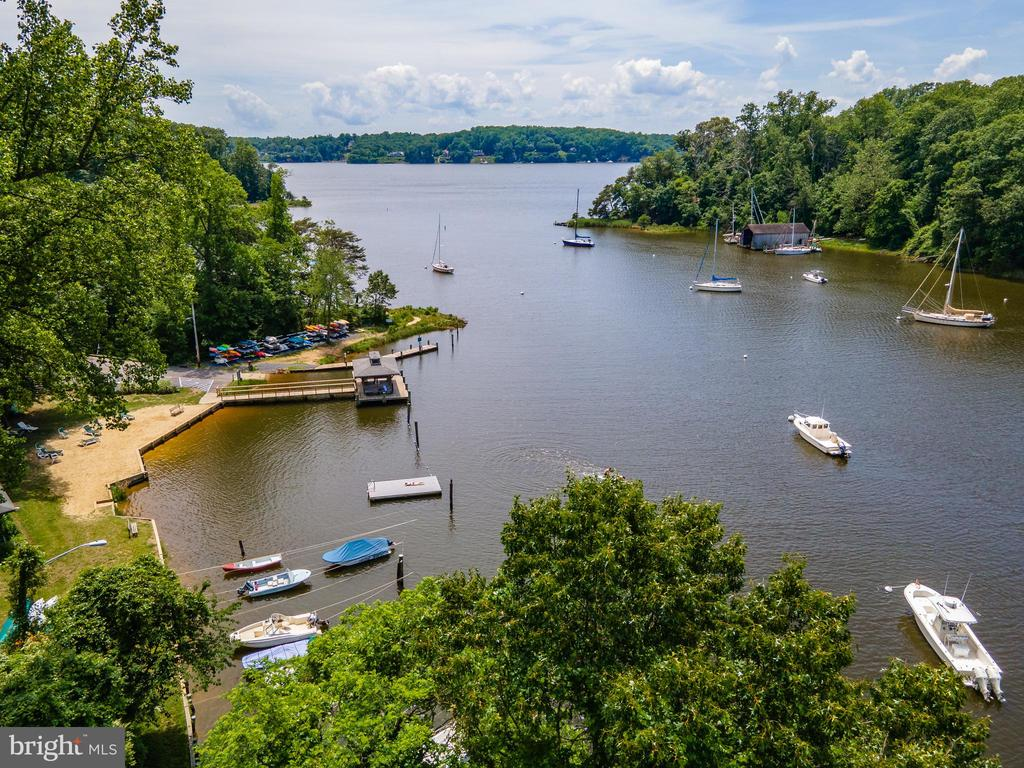 Pleasantly perched on a waterfront bluff with breathtaking, panoramic views of Chase Creek, this completely renovated charming cottage in Pines on the Severn provides the perfect turn-key escape.  This home features the highly sought-after western facing water view which delivers the ultimate vista to savor glorious sunsets melting into the Severn River.  Stroll past the picket fence, up the stairs to the quaint front porch and into the light filled foyer where it becomes immediately evident that this is a truly special home.  Walls of glass showcase the million-dollar water views.  The attention to detail and the custom designer touches throughout bring a true sense of warmth and style.  This is essentially a new home, decked out with top tier finishes, appliances, windows, doors... Totally move in ready plus public water & natural gas!  The main level features an open floor plan with gleaming luxury vinyl plank flooring throughout.  This 2 bedroom, 1.5 bath home feels open and airy and the gourmet kitchen with granite counters and chef grade appliances connects nicely to the waterside living room.   Just off the kitchen, dine al fresco and soak up the views of the Severn river from the waterside composite deck.   The waterside flat yard and the new paver stone elevated patio with gas firepit is the perfect setting for outdoor entertaining.  Quickly access the community beach and marina from the staircase which sits right at the edge of the property.  The lower level offers endless options for additional living space or storage space.   The Pines on the Severn amenities are second to none including a boat ramp, marina, sandy beach, playground, canoe/kayak storage, basketball and tennis courts, nature trails, the Chase Creek swim club and the scenic B&A Trail is .5 miles just up the street. Don't forget to bring your boat!! Your fellow mariners will be envious of the close proximity from your doorstep to some of the best boating/fishing/entertaining the Chesapeake B