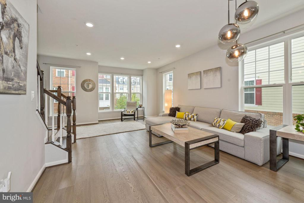 A remarkable new (2019 built) three-level end-unit townhouse in Totten Mews community of Brookland/Fort Totten. Walk to Fort Totten metro and enjoy an easy access to Brookland locations, Catholic University and more. The house is filled with natural light from its many large windows on three sides, featuring 9 ft ceilings. There are three en-suite bedrooms (one on the entry level and two on the upper level). An open main floor boasts an amazing kitchen with custom (dual color) cabinets and top grade custom quartz waterfall countertops and backsplashes, upgraded appliances, dual oven, butler's pantry, custom lights and recessed lights. Enjoy quiet evenings on your spacious deck facing the tree tops behind the community.  Or have a cookout party using the natural gas outlet to connect your gas grill (no propane tank required!). Durable wide-plank hardwood floors throughout. Spectacular bathrooms with quartz and natural stone countertops and custom design features. Upgraded high capacity front loading washer and dryer on the upper level. Custom shelving in master closet. Attached one-car garage with a window, additional storage shelves, and upgraded tile floors. Low HOA fee, HOA manages all landscaping including around your house. The community has a little playground for the kids, plenty of green space for your pets to enjoy, and a walk path to Fort Totten metro for those who have to get back to the office or school.