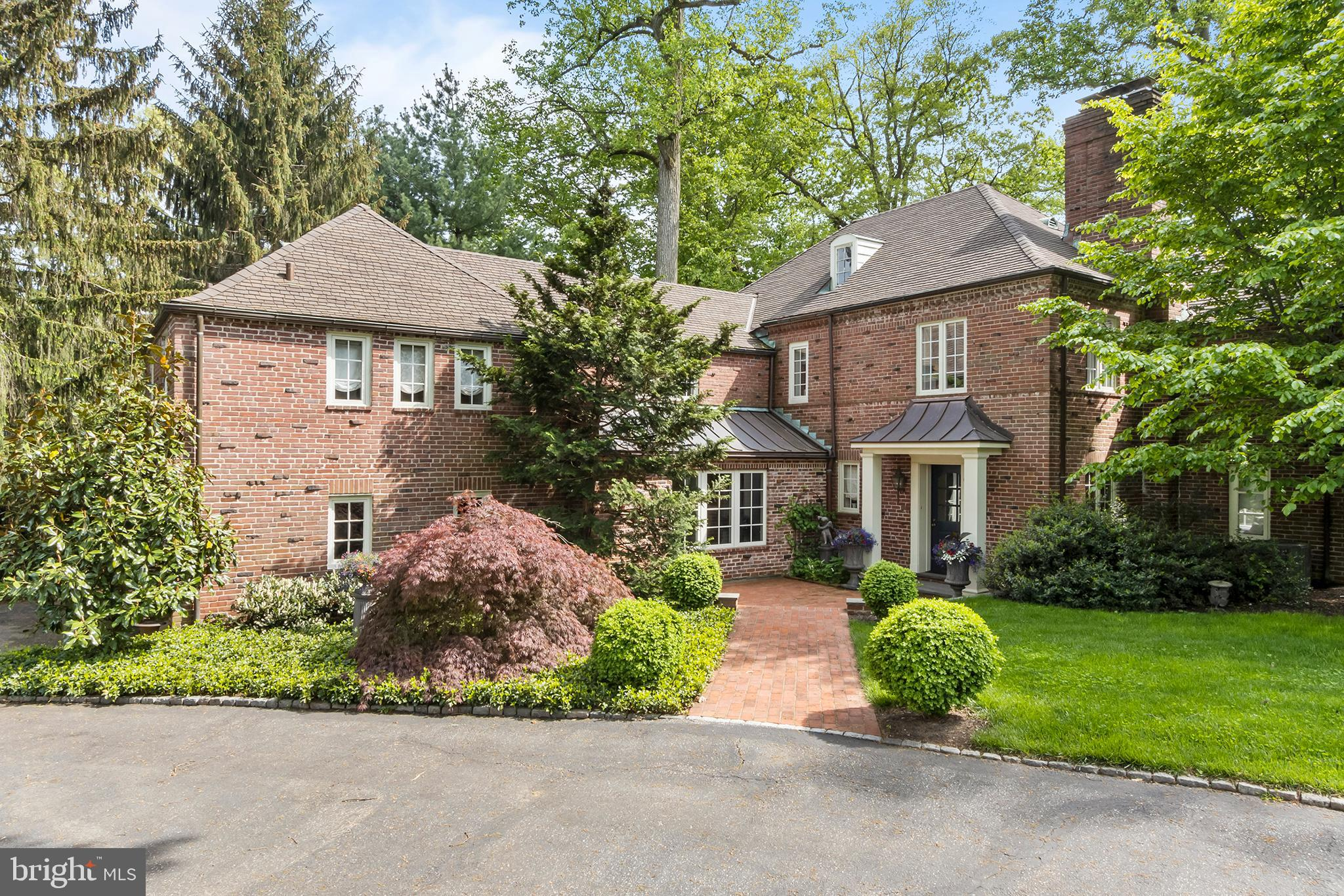 With no detail left undone, this exquisitely restored four bedroom colonial truly encompasses the best of luxury living in Montgomery County. With stunning curb appeal, beautifully landscaped grounds, and a charming brick facade, you'll instantly feel at home upon approaching 235 Cheswold Lane.   Enter into a grand foyer adorned with an antique fireplace, original wooden wall paneling, and a powder room. Rich wood floors, recessed lighting, and decorative moldings are just some of the desirable features showcased throughout the main level. Fit for a chef, the kitchen offers custom-appointments, including elegant white cabinetry, an expansive large center island with a breakfast bar, dual-tone upgraded countertops, a large farmhouse sink, and top-of-the-line stainless steel appliances. One of the most serene aspects of this residence is the light-filled breakfast area boasting several arched floor-to-ceiling french doors that open to your backyard oasis. Complete with a spacious patio, oversized flat grassy yard, shed for added storage, and a stone fire pit, your friends and family will never want to leave this tranquil outdoor space.  Off of the kitchen, you'll find a built-in wet bar and a bright formal dining room showcasing an arched doorway and several large windows. Perfect for curling up with a good book, the light-filled living room has custom-built ins, another opulent fireplace, and a picturesque window seat that overlooks the rear of the property. Concluding the main level, there is a back staircase, bonus door that leads to the back patio, and a second front door that opens into a mudroom.  Serving as your private getaway, the primary suite enjoys a lavish dressing room with a custom-built vanity and shelving, and an ensuite marble-appointed bath with a dual sink, soaking tub, and glass enclosed stall shower. The remaining three bedrooms have ample natural light and excellent closet space. Two of the guest bedrooms share a jack-n-jill designer-appointed b