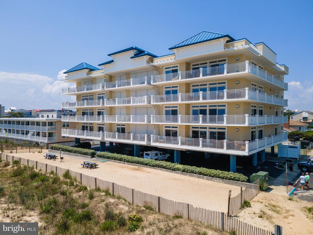 Direct Oceanfront End unit 4 bedroom 3 1/2 bath home with ENORMOUS wrap around balcony in exclusive uptown location.  Situated in a quieter part of town, this home boasts a private beach area between this  building and the dune just for these owners.  Covered assigned parking and ground unit storage are just a start.  Hop in the elevator for easy access to this home or use the stairs if you wish.  From the moment you walk in the front door, walking over the large custom tile flooring,  you will notice how one room flows into the next. Notice the substantial kitchen, with a granite on every surface including the large curved bar, which offers extra seating and a front row look as to all the happenings here .  Custom cabinetry and tile backsplash accompany the double oven and 5 burner GE Profile Gas stove.  There is an extra smaller for fridge for beer and wine or whatever you would choose.   Expansive views from this enormous wrap around balcony that allows you to enjoy all parts of the day. Gas fireplace in the living area to allow you year round pleasant visits to the beach. Huge master suite with steam shower and multi head custom tile large walk in shower.  Double vanity as well.  Faux painting on the walls through out.  Full utility room w. ironing board.  Plenty of storage in this home and room for your family and guests to be comfortable. Make an appointment to see your next home today!