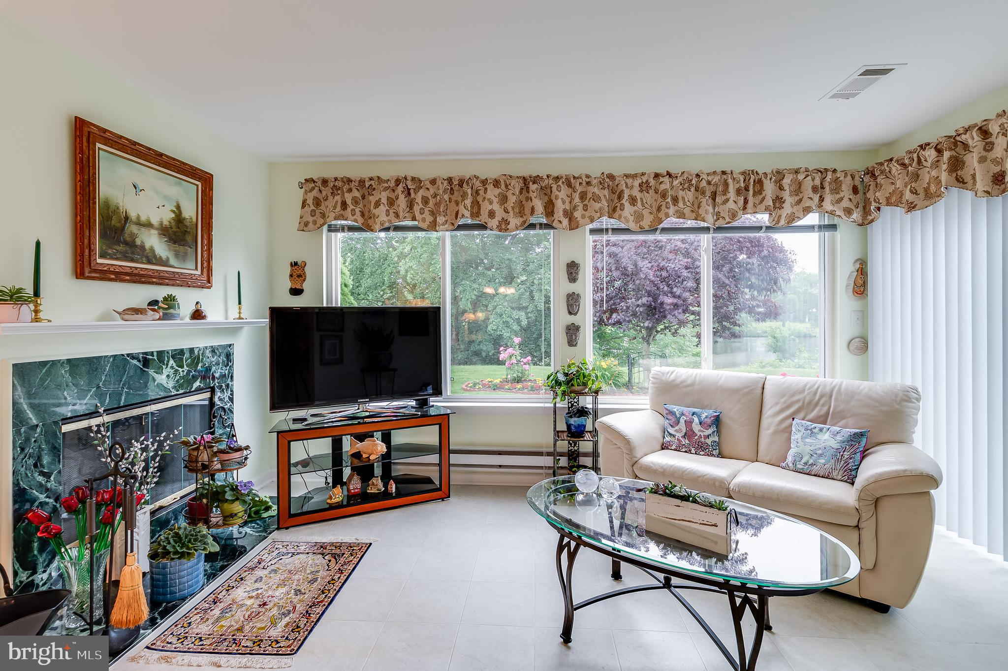 """How absolutely FABULOUS is this WATERFRONT,  EXPANDED Gladwyne model with 1270 Sq. Ft. of Worry- Free Living?? Where to Begin?? How about if we start with a walk up the Concrete Driveway to your Welcoming Porch and then through the beautiful, updated front entranceway. Once inside, your eyes will be immediately drawn to the gleaming Mahogany-toned Engineered Hardwood Flooring, which runs throughout the Living Room, Dining Room, Hall and both Bedrooms. The Living and Dining Rooms have an open floorplan which offers airiness and flow for entertaining. Speaking of Entertaining....as you move into these rooms, you will then be impressed with the 10 x 14 Sunroom with STUNNING, sweeping views of Canterbury lake, which can be seen from virtually every room of this home! Leading from the Dining Room, this Exquisite Room features a Wood Burning Marble-faced Fireplace with Glass Doors. Shelving above gives space for your decorative items. Sliding Windows offer Relaxing Views of both Garden and Lake.  There is an additional Pantry/Storage Closet for convenience. The Brightness of this room extends into the home.  Sliders lead to a Stamped Concrete Patio with an """"Aristocrat"""" Retractable Awning that will provide you and your guests endless hours of pleasure. The Beautifully maintained Gardens are a Delight!  Moving back inside, the nicely-sized Kitchen, which also has a window view into the Sun Room and lake views, offers updated Wooden Cabinets, Updated Appliances, Recessed Lighting and a modified Half-wall/Counter for both a quick bite and that coveted Counterspace!! The Fresh Blue Countertop makes this Kitchen just POP! Moving down the wide Hallway, you will pass a Laundry Center with 2020 Washer & Dryer. The Main Bath has been updated and is Bright and Airy, as is both the Primary Bathroom with not one, but TWO closets. This is no commonly found in a Gladwyne model. The Updated Primary Half-Bath is Clean and Refreshing. The Second Bedroom with amazing light, can be utilized """