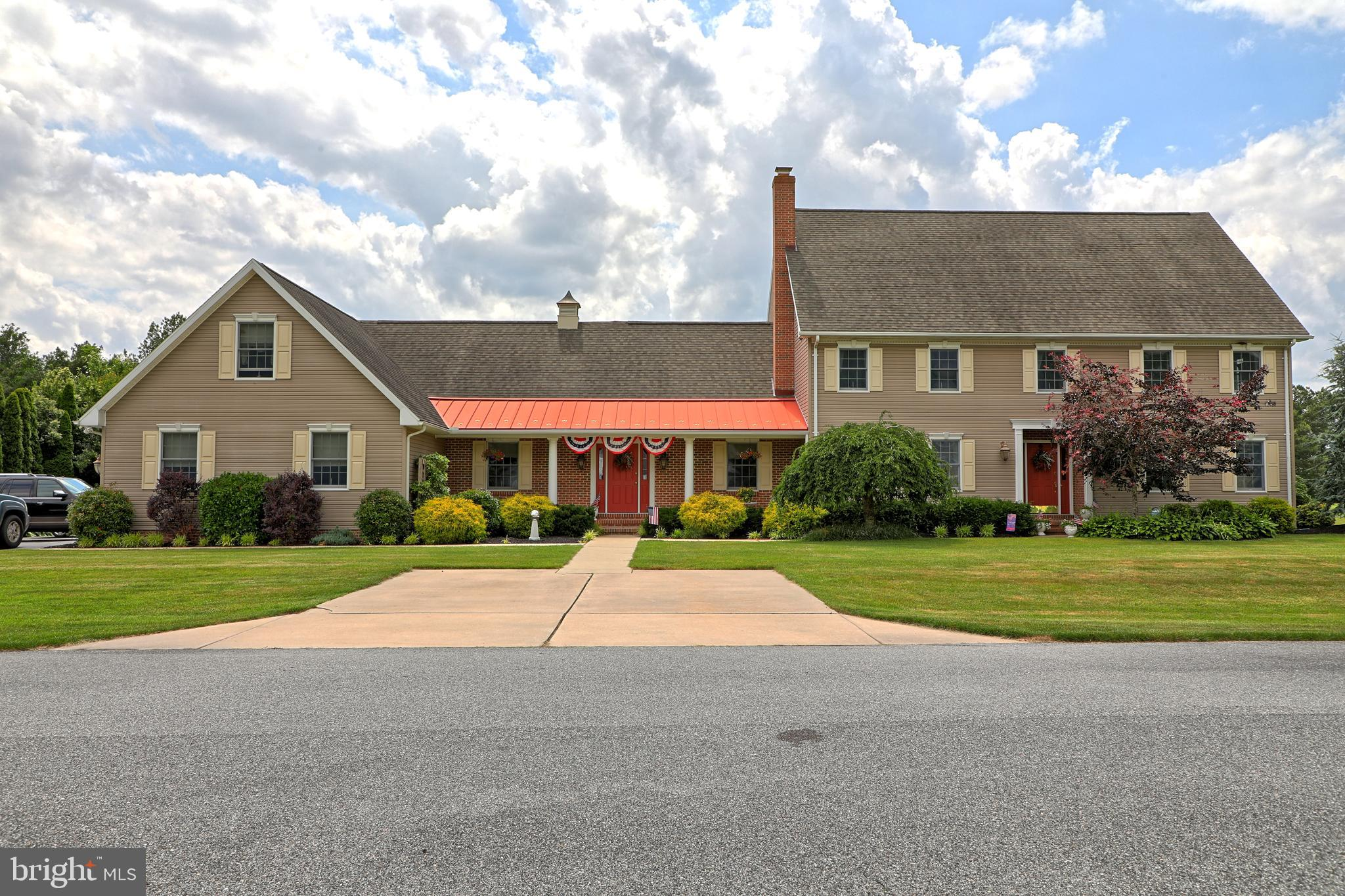 Nestled in the peaceful community of Country Club Village, this breathtaking 4 bedroom 3.5 bathroom colonial-style home is situated just off the 7th tee, on one of the largest lots in the cul-da-sac. Boasting over 5800 square feet of living space on a generous 0.63 acre lot, this home has been meticulously maintained with convenient upgrades for the modern homeowner and was elegantly designed with the concept of family being the top priority. Upon arrival, you're greeted by the lush landscaping and cozy front porch with brick accents, which will quickly become your favorite spot to sip coffee as you watch the sunrise. Ravishing hardwood flooring flows throughout the multiple living spaces and further accentuates the rustic charm of the home. Cozy up with your favorite book or your loved ones next to the floor to ceiling, brick fireplace in the family room or head to the kitchen and let your inner chef inspire you! The spacious, gourmet kitchen highlights ample cabinet and counter space, stainless steel appliances including a four-burner gas range, large pantry and a generous center island. Unwind after long days in the spacious, second level owner's suite with a gorgeous California closet with ample storage space as well as a luxurious en suite bathroom equipped with a dual vanity with granite countertops, a standing shower and a relaxing soaking tub. The home also features a gorgeous, attached in-law suite with a separate entrance, living space, kitchenette and bedroom, ideal for guests staying over night. Offering two more additional bedrooms, a large bonus room that can be converted to fit your families needs, as well as another full bathroom, this home has plenty of space for all your loved ones! Spend your days soaking up the sunshine on the back deck surrounded by beautiful flowers, herbs and raised garden beds or head to the paver patio and relax in your lawn chair with your favorite beverage in hand. Once the sun goes down, hop in the hot tub and watch the f