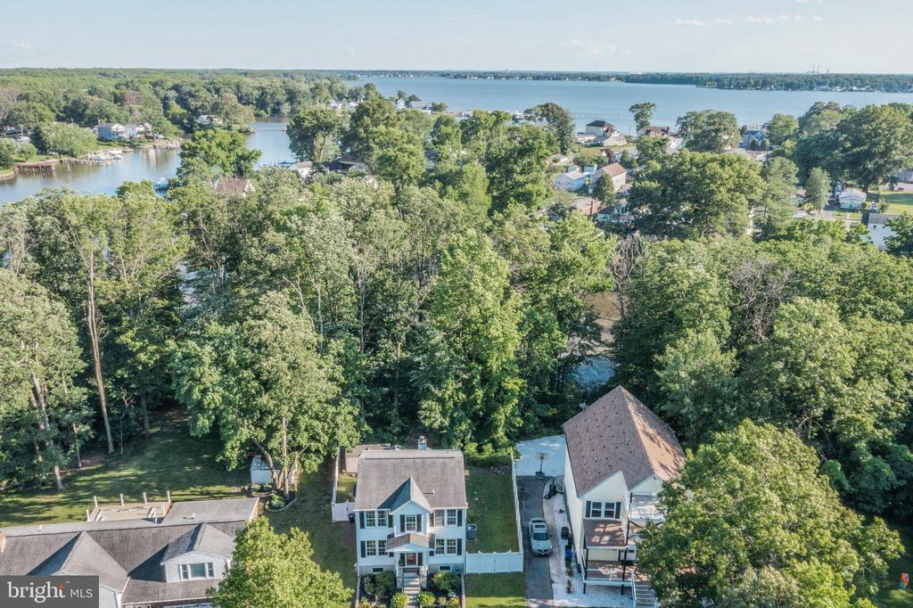 This beautifully updated, move-in ready colonial with nearly 2,000 square feet of finished living space is located on the water. Enjoy living in this sun-bathed home with wood floors, new paint inside and out, and carpet. The family room with a wood burning fireplace overlooks the back yard and offers scenic views of the water as well as access to the deck and back yard. You will love meal prepping and entertaining in the large, updated kitchen with painted cabinets, newer appliances and plenty of space for dining. Wood floors run through the living and dining rooms, which are graciously finished with crown molding and chair rail. A laundry room and half-bath complete the main level. New carpet runs up the steps and throughout the second level. Upstairs, the primary bedroom features a walk-in closet as well as an updated bath with a jetted tub and separate shower as well as modern cabinetry. Two additional bedrooms and a full bath finish the upper level. The basement offers an additional 1,000 square feet of space ready to finish and opens to the back yard. The back yard has a paver patio, a shed, is fenced in and has a path to the water. Enjoy the water views by the fire pit or drop your boat into Muddy Gut and enjoy life on the water. Located minutes from commuting routes, shopping and more, this home has it all. Welcome home!