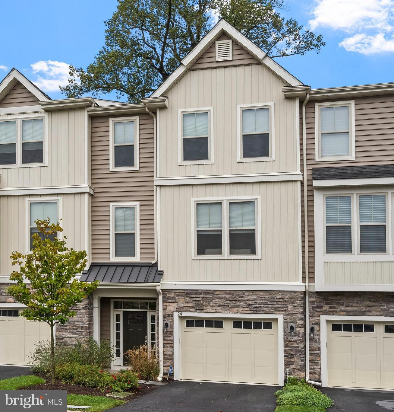 Do you dream of living in a newer Main Line home built by one of the area's most sought-after builders, but you don't need a huge single home? You will love this Bentley-built townhome, right on the Main Line in Paoli. Convenient to everything the area has to offer, Paoli Walk is a quiet and small community surrounded by mature landscaping and a walking trail, just minutes to the Paoli Train Station with direct Philly and NYC trains daily, the Paoli Hospital, Paoli Village Shoppes, Valley Forge Park, dozens of business parks, and so much more! This is easy living at its finest! There is nothing to do here except unpack, sit back, relax, enjoy some Netflix on the sofa, coffee on the deck, a little work from your home office, then head out for the night – or even head out on vacation – without worrying about taking care of the yardwork or maintenance. Bentley Homes is known for their top-notch craftsmanship and building properties with the discerning homeowner and their lifestyle in mind. Tall ceilings, beautiful woodwork, hardwood floors throughout, high end finishes, and a modern flexible floorplan are just the beginning. The entry level greets you and your guests in a cheery foyer with a custom crafted bench area for coats and shoes. This level was recently upgraded to include a new bonus room and a new powder room, and has direct access to the garage. Upstairs the main level features an open layout, floor to ceiling windows, and sliding glass doors to the private rear deck overlooking the woods. The spacious chef's kitchen offers endless counterspace for entertaining, or to enjoy the company of a few sous chefs while preparing everyday meals. Just beyond the kitchen is a dedicated office that overlooks the front of the home, and a stylish powder room with upgraded fixtures, vanity, marble countertop, and lighting.  The upper level hosts the primary bedroom suite with two spacious closets, a luxurious bathroom with a private shower/toilet room, linen closet, a doub