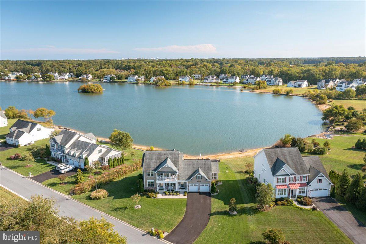 Striking 5BR/3.5 BA waterfront home in sought after Hamlet at Dirickson Pond hits the market!  This amazing home has an abundance of outdoor space and backs to a spring fed pond that allows non-motorized boating and catch and release fishing, which you can do right from your own private beach.  Launch your kayak, canoe or pedal boat from the pond out back.  The community also has an outdoor pool and clubhouse and is located less than 7 miles from Fenwick Island and Bethany Beach.  The home has an open floor plan and a two-story family room with an impressive wall of windows with an abundance of natural light and expansive view of the pond.  There is also a gas fireplace for relaxing during chilly nights making this the perfect home for year-round enjoyment.  The gourmet chef's kitchen is off the family room with upgrades including custom cabinets, quartz countertops, custom backsplash, stainless steel appliances with gas cook top, center island, large pantry, breakfast area, energy efficient appliances and wood floor.  Directly off the kitchen is another dining area and a sunroom flows off the kitchen as well and makes the perfect spot to relax or for use as a home office. The oversized waterfront master bedroom is on the first floor with expansive water views. The large master bath has his and her sinks, large vanity makeup area, large custom tile shower and spacious walk-in closet.  On the first level you will also find a powder room and laundry room.  On the second level you will find 4 more spacious bedrooms and 2 baths, and one of the bedrooms has a private balcony.  Outside there is a large screened in deck perfect for relaxing or enjoying a barbeque or crab feast. There is also a second deck with an  oversized hot tub overlooking the water.  The large backyard leads to the pond.  You will fall in love with the extensive hardscaping and landscaping surrounding this beautiful home complete with irrigation. There is a storage area below the home with access from