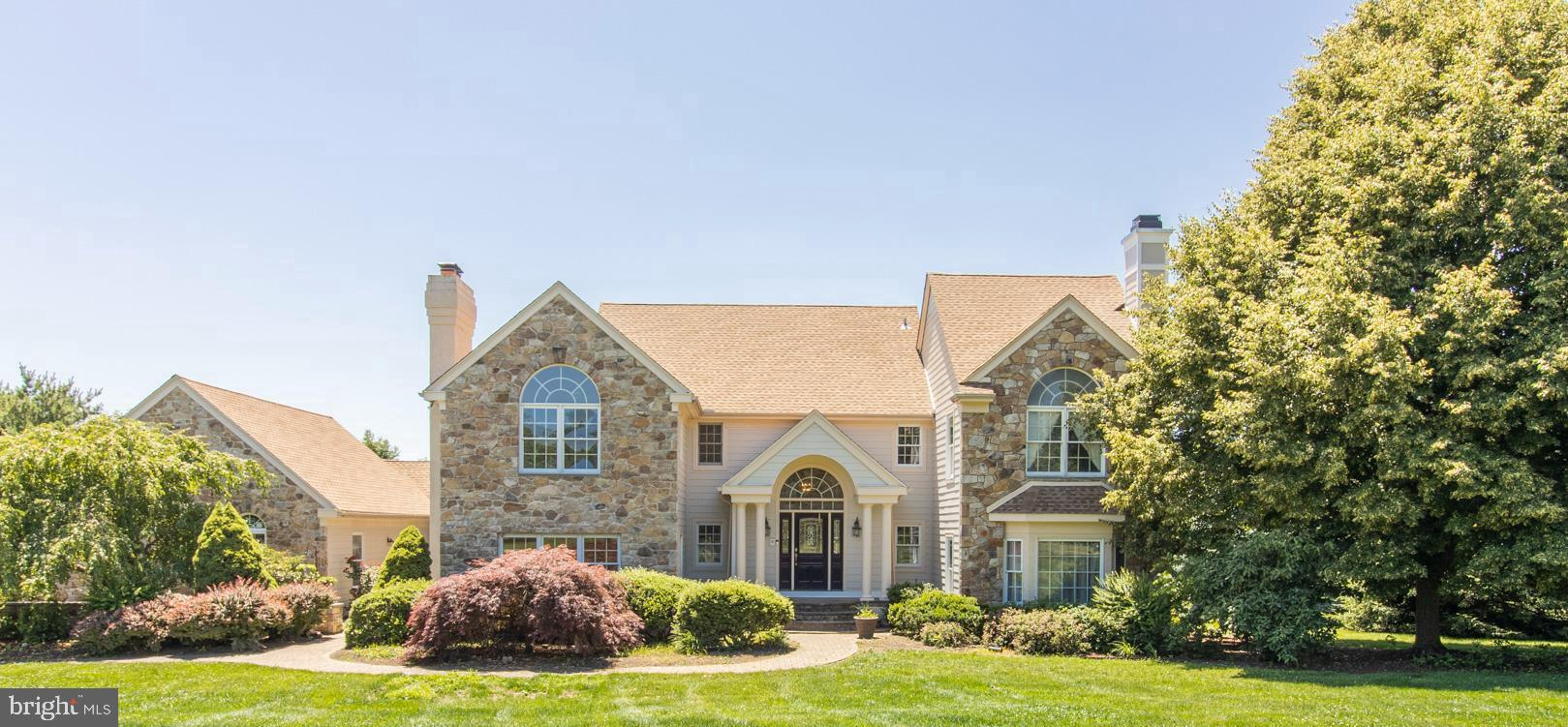 Timeless & Classic describes this Estate styled beauty. Loaded with  every amenity and convenience you have been searching for in a home. This home has a first and second floor owner suite. Enter the home into the raised entry foyer where you'll enjoy the view of the open two story family room highlighted by the two story stone fireplace that is currently gas burning but can be converted to wood burning. Another great feature is the  wet bar and hardwood floors. A few steps away is the oversized eat in kitchen with million dollar views of the back yard space. Large number of oak cabinetry and a huge wrap around two tiered corian countertop, a wonderful appliance package and exits to a beautiful courtyard.  The dining room  trim package includes crown molding and wainscoting that can be made more private behind french doors. This room's other great feature is the private exit-way to the courtyard, perfect for enjoying a meal outside. Looking for a 1st floor Owners Suite? The search is over! This huge 22x22 Owner's Suite offers a walk-in closet, garden spa tub and huge walk-in shower and double door access to the rear deck. Just the retreat suite you dream of.  The parlor/living room features crown molding, wood burning fireplace and lots of natural light , and to top off the first floor you have a large office or den with a gas fireplace.  Another wonderful upgrade design is the  first floor laundry room with built-in cabinets. The second floor boasts 4 large bedrooms and 3 baths and features cathedral ceilings, huge closets. Additional bonus storage is the access to the attic.  The full unfinished basement offers a walk out door to the back yard and tons of natural daylight.  The future opportunities for this space  are endless .  Other features: New exterior renovations made with stone and Hardie Plank siding with bluestone flagstone accents. 10 year transferable warranty from the time the home transfers from current homeowner. Upgraded install features were done t