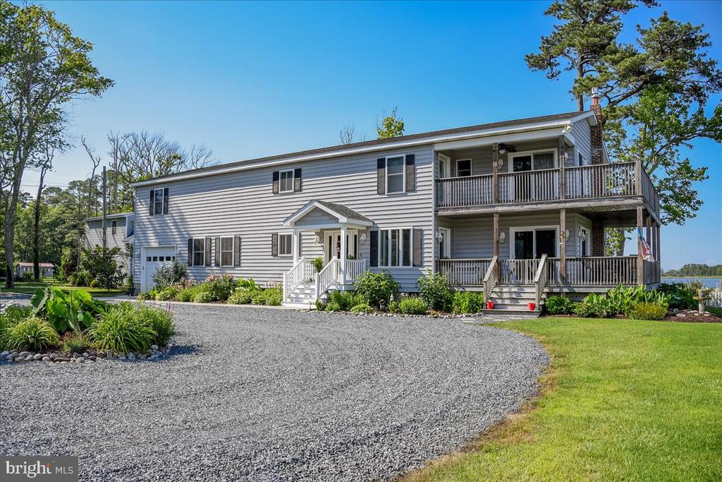"""If you desire to live on the water in West Ocean City with privacy and seclusion, this home has a long list of extras seldom available. The home site is  0.5+/- acre of water front on Herring Creek, a tidal tributary into Isle of Wight Bay. The average water depth is 3' to 4' at center line, recommended maximum 30' boat length. The property is located on a private driveway serving neighboring houses, accessible via Route #50 West, within 10 to 15 minutes of the Beach Resort yet quiet and serene with a wide open water view. The house was rebuilt in 2013  with quality appointments: 2 zone HVAC systems, elevated foundation, majority new widows, sliding glass doors, wrap-around porch, wrap-around deck, full equipped Kitchen with gas cooking, ceiling fans, hardwood flooring, gas fireplace, water heater, lighting, equipped laundry and so much more. The property also offers a detached Boat House, 3 storage sheds, some fencing, attached Garage, mature landscaping.  no HOA fee. For Buyers who prefer a small Community without restrictive HOA covenants, an """"independent thinker"""", this may be your new paradise."""
