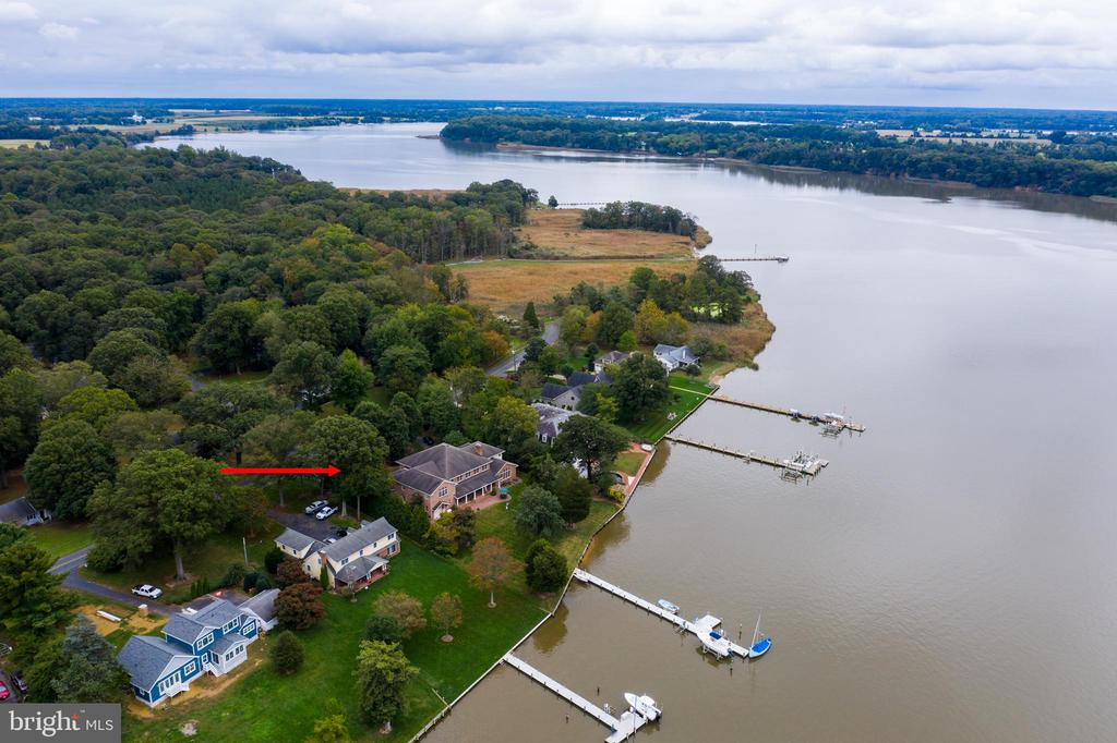 Spectacular classic Georgian style 5 bedroom  home located on .88 acres with approximately 150' of waterfront.  As one enters the home, the immense hallway directs you to French doors on to a  brick porch, yard and then dock on the Chester River.  The  130' dock  holds 4 boat lifts, one 12,000pd lift.    Nothing was spared in the construction of this extraordinary home.  All brick exterior built with flood plain construction.  Heated heart pine floors and custom tile, heart pine built in cabinets, spacious kitchen with breakfast bar,   separate dining room and informal eating area off the kitchen. Two staircases leading to the 4 bedrooms, 3 with ensuite bathrooms,  large gathering area and spacious TV room which is currently used as. First floor master suite, with large master bath, custom built in closets. and access to the waterside porch.  Office with built in cabinets.  Separate entrance by the waterside to a powder room and laundry area.  Kitchen is also accessed by the garage.  Too many amenities to mention. A must see. Enjoy  all kinds of vessels sail or power up to Chestertown, the home to the Down rigging  of the Sultana Weekend,  what a site to see these tall ships  come in for the weekend in Chestertown in the fall.