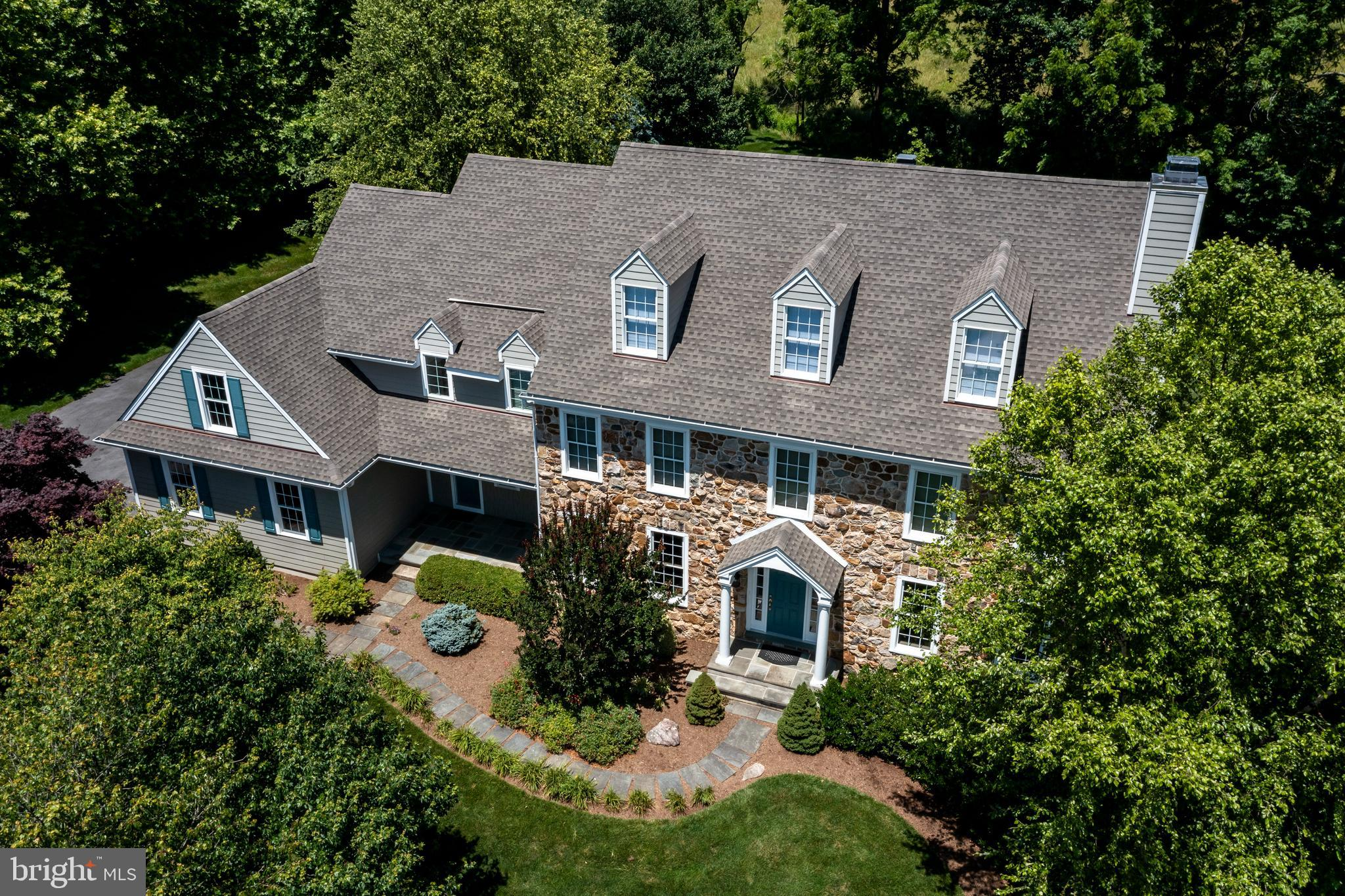 Welcome to 17 Peale Drive   the very best of Chester County – town & country!  Built in 2003, this modern traditional, stone-front, colonial is located on a level cul-de-sac lot in Olmsted that feels like a tranquil park setting - with the perfect mix of open lawn, deck, patio, evergreen and shade trees.  You can choose to enter through a 3-car, turned garage, or through the side porch into the mudroom and laundry area – which has gas and electric options, and bead-board millwork with a chair rail.  Greet guests under the covered front porch and usher them into the grand foyer with hardwood floors, crown molding, and coat closet.  Off the foyer, a spacious powder room includes a private water closet.  The large formal living room was bumped out by the builder, and features crown molding, wall-to-wall carpeting, recessed lighting, and a gas fireplace.  The first-floor office has French Doors with a transom window, wall-to-wall carpeting, recessed lighting, and two sets of built-in cherry cabinets and shelves.  This attention to detail is carried on in the dining room with hardwood flooring, a chair rail, crown molding, and chandelier.  In the kitchen you'll also find hardwood flooring, farmhouse white and cherry cabinets with glass front accent doors, a center island with overhang for bar seating, granite countertops, stone backsplash, gas cooking on the range with a double oven, pendant and recessed lighting, a roomy eat-in area for casual dining and wet bar for entertaining ease.  The sunroom is directly adjacent to the kitchen, also with hardwood flooring, large windows, and a sliding door that opens to the TREX deck, walkway, and stone patio complete with a large pergola.  Back inside, the family room has a vaulted ceiling, recessed lighting, wall-to-wall carpeting, and a wood burning fireplace with stone surround.  A back staircase provides convenient access to the 2nd level.  Upstairs, you will find wall-to-wall carpeting in the hall and bedrooms.  The primary 