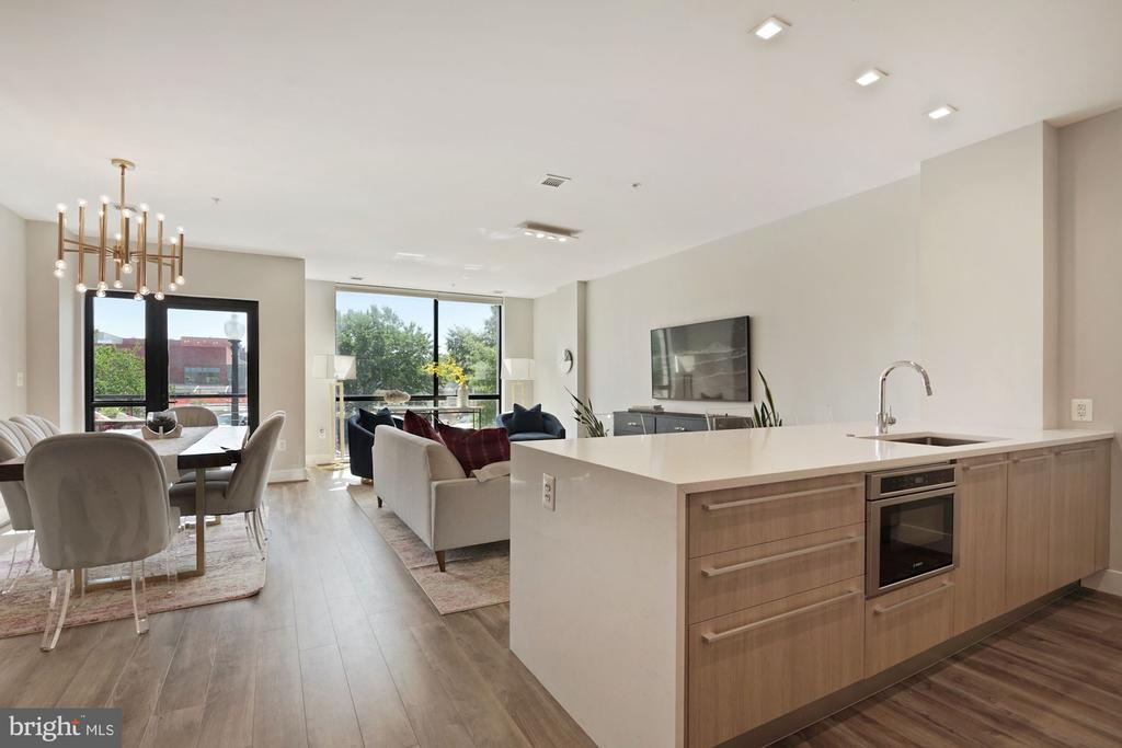 Stunning brand new construction in 2017 (only occupied since 2019) in Logan Circle. Unit 102 is an exquisite home featuring oversized floor-to-ceiling glass, soaring ceiling heights, Austrian wide-plank flooring, solid core doors, designer hardware, ample storage & walk-in closets throughout, recessed LED lighting, programmable thermostats, custom millwork throughout, and a private balcony. The Chef's Kitchen offers custom European cabinetry with soft close doors & drawers, Caesarstone countertops with full-height backsplashes, deep single bay Kraus kitchen sink, under cabinet lighting and a Bosch appliance package including a gas range, convection oven, panelized refrigerator and dishwasher. The spa-inspired baths feature Porcelanosa tile, Waterworks fixtures, large showers with frameless glass doors and Kohler soaking tubs. A garage parking space (separately deeded), extra storage unit and bike storage conveys with Unit 102.  The Residences at 11Park features solid concrete construction with a grand two-level lobby with fireplace, fitness center, owner's rooftop lounge, roof deck with grilling station, underground garage parking, secure private storage units, private bike storage & service station, pet grooming station, eco-friendly green roof and directly across the street from the brand new dog park and playing fields.  Square footage estimate based on developer's plans. $500 credit for using KVS Title.