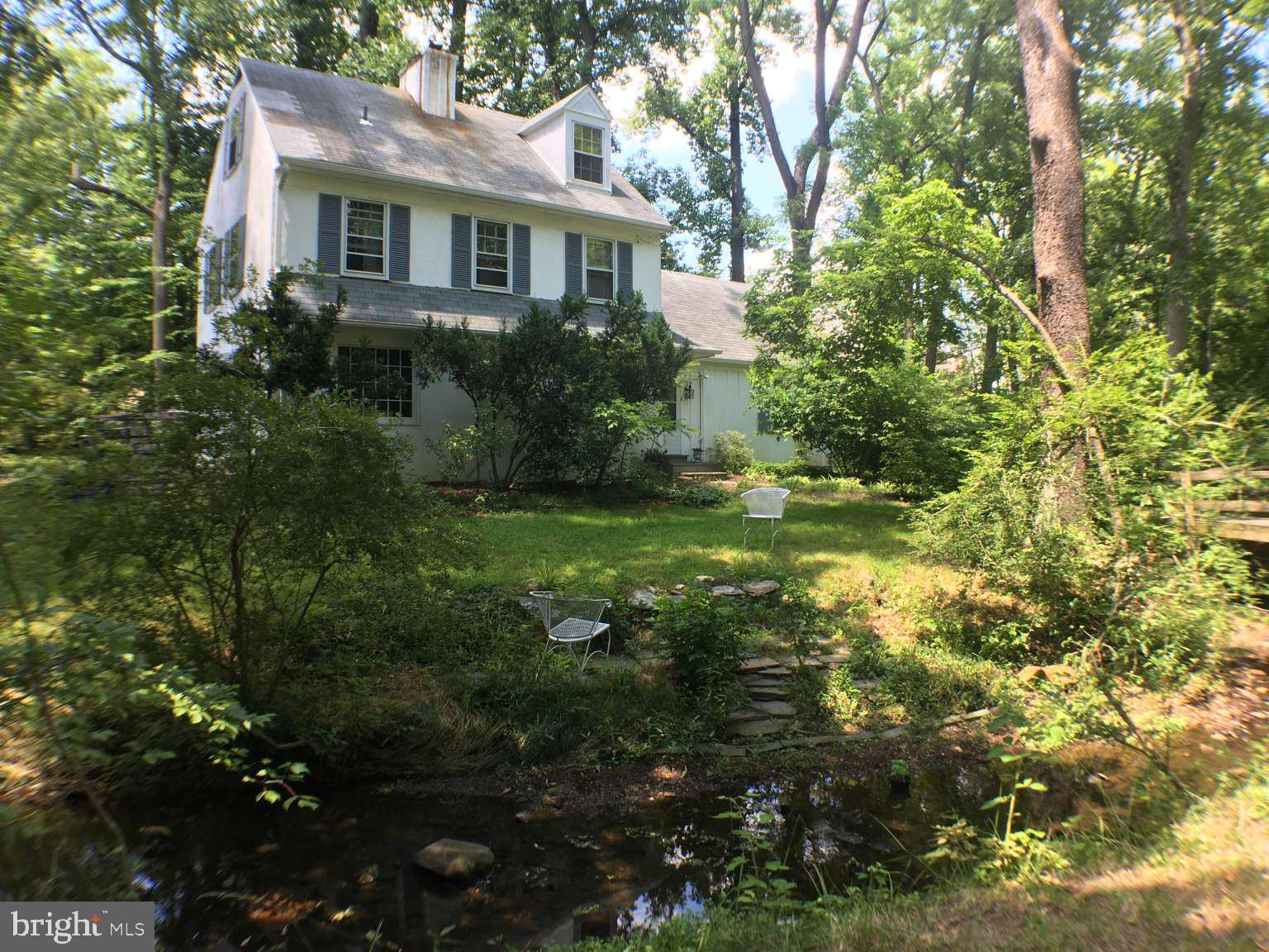This family home was built in 1960 by noted Main Line Builder Bob McElroy. A farm house style Chester County home on a large five-eighth acre lot, it is move in ready with room for your style and changes. A private woodland setting offers 360 degrees of beautiful views out every window. The highlight of the property is sparkling Julep Run Creek, right in the front yard. No other property in the area boasts this highly unusual and captivating feature. You will be gazing into shimmering water every day while you sip your morning coffee in the dining room. IMPORTANT--no flood damage to this house EVER. We have not experienced an issue because we do not have a basement. The dining room boasts a polished brick floor and ceiling beams. Two substantial brick fireplaces will warm you with wood burning fires in fall and winter, one in the living room and one in the dining room. French doors, and authentic windows with real wood mullions grace the architecture. Beautifully refinished hardwood floors throughout the entire house complete this solid, cozy home. Enjoy a kitchen built just three years ago and an an added laundry room. The attic off the master bedroom could be converted to a formal changing room, studio or office. A family room with closet downstairs could easily be a fifth bedroom - bathroom right around the corner. Lastly, a bridge spans the stream (accommodating over 14,000 pounds of weight) so you can park in the front or rear of the property. This family home gave us 60 years of cherished memories with nature all around. Located in the award winning Tredyffrin-Easttown school district; it is one of a kind.