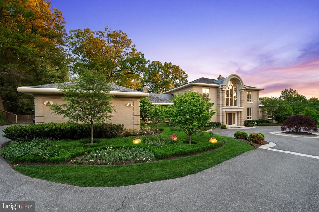 Located adjacent to the cherry-blossom-lined streets of the Kenwood neighborhood, and perched upon two private acres of lush landscape, this incomparable, seven-bedroom, 11-bath, architectural masterpiece offers the best of all worlds, including a secluded, resort-like setting located within a 10-minute walk to downtown Bethesda.  With a luxurious, main-level, primary suite, three fireplaces, a three-car garage, an indoor pool with dual showers and dressing areas, a professional-size putting green, a media room, two hobby workshops, and a coat room for large-scale entertaining, this extraordinary property is already beyond compare. But the true beauty of this home is the thoughtful balance of casual and elegant, voluminous and intimate, contemporary and timeless, and its ability to comfortably host a few dozen guests for a formal dinner party or a dozen kids for a birthday celebration. This house lives large but functions beautifully on both levels.  A clear sense of entry into the home is instantly established by the gentle curve of an elegantly arched window on the front façade that echoes a similar, two-story arched window on the back of the home; both flood the interior with natural light. The back of the house is constructed almost entirely of glass, which provides sweeping vistas of the pristine and polished landscape. Except for storage areas and a pair of powder rooms, every space of the house has an outdoor view. The meticulously manicured and maintained grounds are verdant and vast, and just as suitable for displaying sculptural artwork as they are for hosting garden parties and family gatherings.  Inside, voluminous yet graceful proportions mingle with contemporary and classic details. A two-story foyer includes a gracefully curved double staircase that leads to the lower level. Soaring, light-color walls, juxtaposed by the warmth of the wood floors, make the interior spaces feel open and airy—almost cloud-like—and offer an optimal setting for displaying 