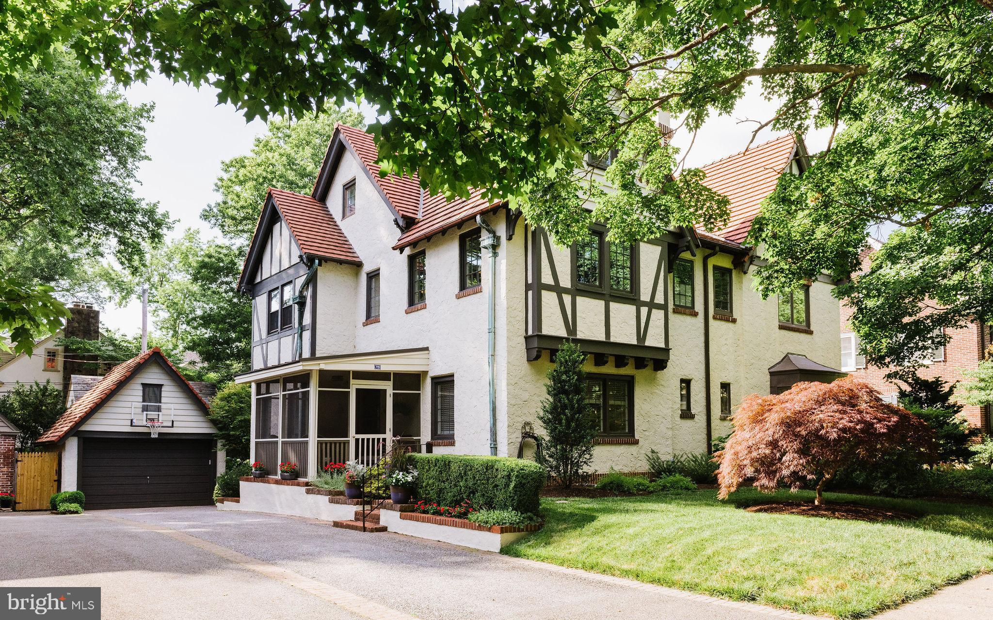 Nestled in highly desirable and historic Wawaset Park, this alluring architectural treasure awaits. Straight out of a fairytale, this storybook Tudor home is characterized by its steeply pitched gable roofs, elaborate masonry chimney, and decorative half-timbering. These details, along with terra cotta roof tiles and copper gutters combine to present an offering of quality, charm and character that can't be replicated today. A Japanese Maple, abundant plantings, and mature trees only enhance the beauty of the facade. Down a brick pathway, one approaches the main entry through a screened-in porch. The gracious foyer is flanked by two architectural arches, leading to the living and formal dining room. Anchored by a brick fireplace and built-ins, the living room presents a stunning coffered ceiling. Both the living and dining rooms have large windows that wrap around 3 sides of this home providing early morning brightness and golden hour calm. The eat-in kitchen boasts a neutral palette, with Jenn-Air stainless appliances, coffee station, and wine fridge. The combination of the cabinets, countertop finishes, and backsplash create a cohesive space. The kitchen windows overlook an exceptional rear yard reminiscent of an English courtyard with a private space to enjoy al-fresco dining and a large outdoor living room area. Fully fenced and with total privacy, the colorful plantings and fountain feature, complete this oasis that is the envy of all your neighbors. Back inside, the second floor has three bedrooms including an owner's suite with walk-in closet, marble bath, custom built-ins, and pedestal sink. There is a shared hall bath and linen closet finishing off this floor.  Up on the third floor, tucked into the roof eaves, there are two spacious bedrooms, hallway built-ins, multiple closets, and a full hall bath with clawfoot tub. The full basement is unfinished and provides great storage, as does the 1.5 car garage with remote entry. Stylishly embellished and impeccab