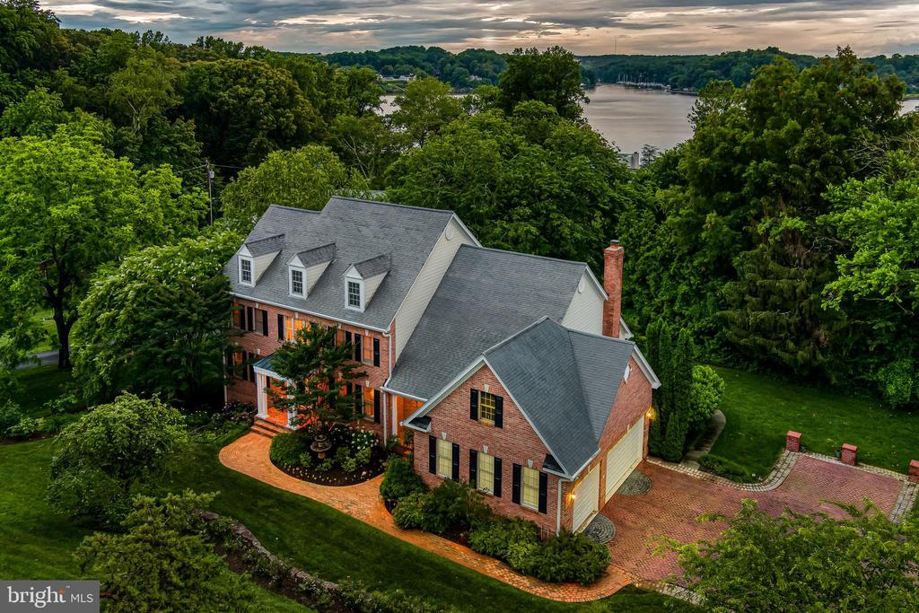 This exquisite six-bedroom, four-and-a-half-bath gracious estate home is ideally tucked away in the quiet and serene community of Ashby. Accessible through a wrought-iron entry gate, follow the driveway to this timeless brick colonial. Boasting a total of over 6,000 square feet, every element of the home is impeccably maintained and infused with the finest materials, fit, and finishes with rich oak hardwood floors, high ceilings, architectural moldings and design-inspired details. Refined principal rooms create a spectacular venue for entertaining, and transition seamlessly to cozy living spaces. The ultra-high-quality interior is functional, elegant and meticulously crafted, featuring a two-story grand foyer with a sweeping curved staircase, elegant formal dining, and a spacious office with custom built-ins. The expansive gourmet kitchen features gleaming granite countertops, stainless steel appliances, a large center island with five-burner gas cooktop and seating, and a dining area with abundant windows.  The stunning family room is outfitted with vaulted ceilings, skylights, gas fireplace and sliding door that allows access to the large deck. The main level also presents the stunning primary suite, perfectly accented by a tray ceiling with custom mural, a gas fireplace,  door leading to the deck, spacious custom walk-in closet, and serene en-suite bathroom with jetted soaking tub and private water-closet. The upper level hosts four generously sized bedrooms, including a junior suite with custom walk-in closet and en-suite bath, and a hall full bathroom.  Continue to enjoy the home's amenities in the finished walk-out lower level where you can relax in the recreation area, gym nook, or take advantage of the private bedroom suite, complete with full bathroom, kitchenette and sitting area. There is also an expansive storage area.  Further enhancing the appeal of this special property are the immaculately landscaped grounds, lower patio, Bluestone walkway that leads