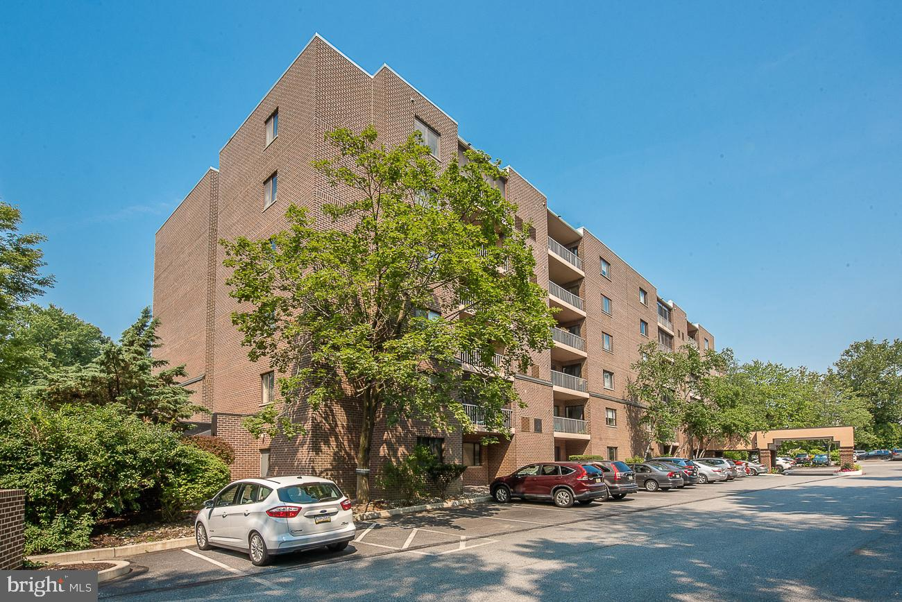 Meticulously maintained first floor unit with sliders out to a rear ground floor patio overlooking the open space with trees and stream.  Beautiful white kitchen with granite countertops and plenty of cabinets for storage.  An open and spacious living room and dining room making entertaining easy and gracious.   Main bedroom with deep walk-in closet and main bath with stall shower.  Second bedroom and hall bath.   Storage locker included too!  The Condo fee includes: Pool usage, water, common area maintenance, trash, exterior building maintenance, landscaping and snow removal.  Beautiful lobby, library and social room on site.  Property has management secured access and doorman everyday from 5 PM to 12 AM.  A coveted location within walking distance to Wynnewood train station, Whole Foods, Wynnewood Shopping Center, Giant Foods, CVS and more.  Enjoy easy living in a park-like setting.