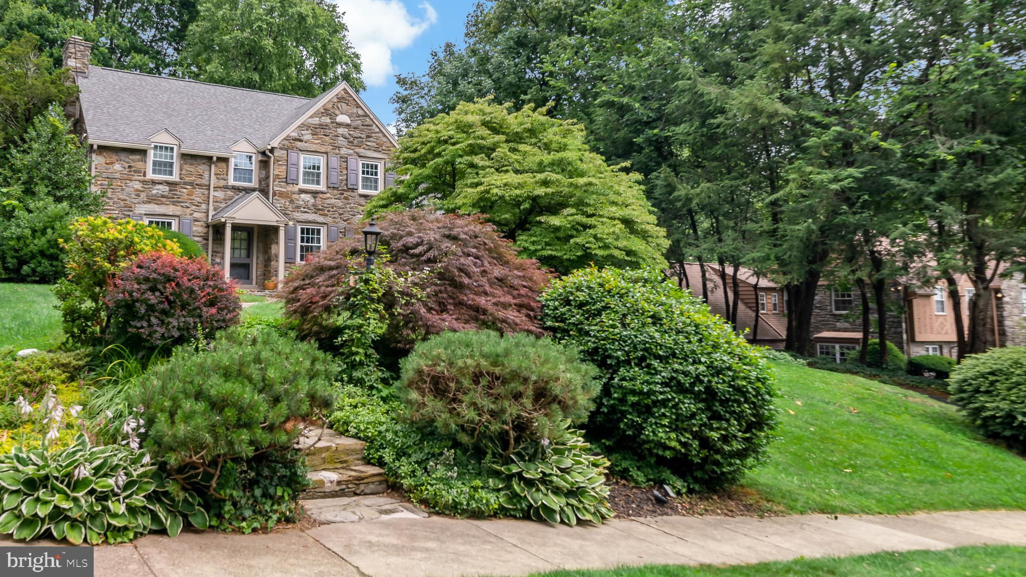 Settle right into this charming stone colonial home in Bala Cynwyd and enjoy comfortable family living in a great location near schools, shops, restaurants and other amenities! The 4 bedroom, 2.2 bathroom beauty sits on lovely landscaped grounds and offers a gracious center hall layout greeting you inside. Wood floors and staircase in the entryway make an elegant first impression. At left you will find a spacious living room with a wood-burning brick fireplace for quiet family nights and entertaining guests. Across the foyer is a lovely dining room for sharing casual and formal meals.  Connected is an enclosed sunroom, with a Southern exposure backdrop, where you can serve coffee and cocktails, or read and relax with a backdrop of lush property views through walls of windows. The kitchen is inviting and lovely featuring stainless steel appliances, tiled flooring, and a sunny breakfast room. From here, glass-paneled French doors lead out to the brick patio for barbecues, summer parties and backyard fun. Also on the 1st floor is a family room converted from a garage for watching TV, playing games and conversing, enclosed laundry, as well as a convenient powder room. Upstairs sleeping quarters offer 4 bedrooms including the serene primary suite with its own private bath. One of the other 3 bedrooms has an en-suite powder room, and the remaining 2 access a full hall bath. Plus there are plenty of closets, a rear staircase, and steps to a generous walk-up attic that can be finished for a 5th bedroom, playroom, or exercise room. Everyone will love hanging out in the full finished basement used as recreation/play space, a workout area and home office, with lots of room for storage. Driveway parking, 2 zoned heating and central air, new roof, water heater and replacement windows, make this well-maintained home a true gem.