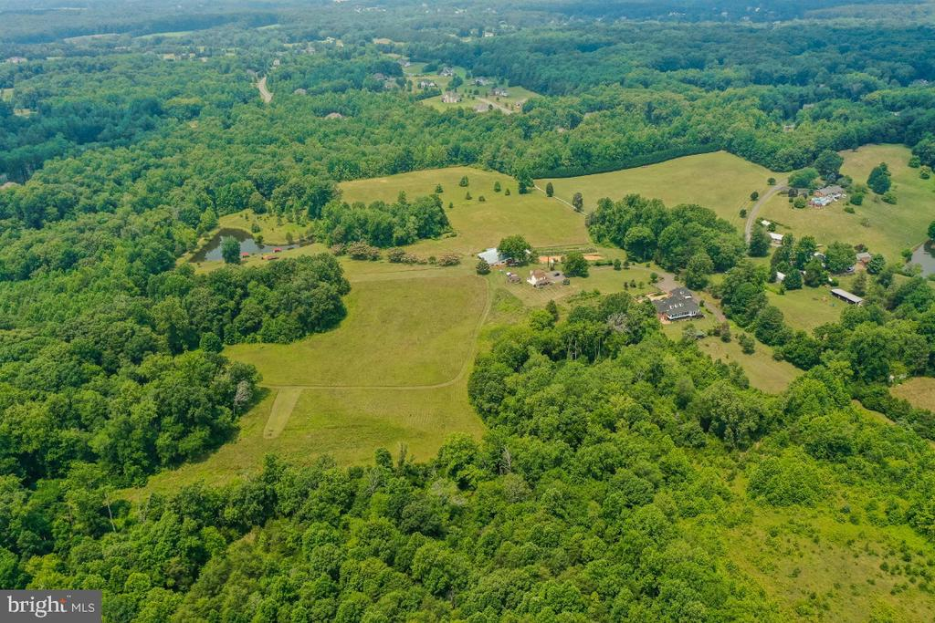 """Beautiful 62+ Acres of Gently Rolling Open Fields and Forested Land, Conveys with this stunning French Provincial home, approximately 4600 sq. ft and a 2nd home approximately 2400 sq. ft. Which  can be used as rental home. There is also another building that can be uses for sepcial events. This farm is being sold """" As Is"""".  The whole property can be yours for $2,700,000 or the seller will consider selling 50 Acres of raw land for $1,700,000.  Subdivision possibilities abound !!!! Surrounded by Estate  homes in Fastest Growing area of Stafford.  Property is presently in land use, buyers can keep in land use, however if they take any of the property and change the use they will be liable for any rollback taes due.  Seller will not pay any rollback taxes."""