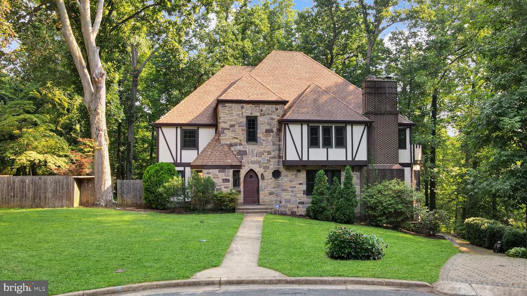 The current owners lovingly refer to this home as 'the Castle.' Once you see it for yourself, you'll see why! This Tudor-style, two-story, five-bedroom home with 2.5 baths is situated on a cul de sac; a stone driveway makes for a beautiful approach to this unique and spacious home. The woods surrounding it offer a sense of privacy and remoteness even though it's located close to Annapolis.   On the first level, the main rooms of this house, with their beautiful hardwood floors, dark trim, creamy color palette, are warm, comfortable, and inviting. The parquet flooring in the entryway adds interest and a textured richness. The living room features a fireplace and a side dining arena; there is also a fitness room, an office, and a sunroom. There is a lovely flow to the first-floor layout, and it is ready for your unique customizations.   The kitchen is open-style with warm, brown granite countertops, ivory-colored cabinetry, and beautiful golden-hued hardwood floors. There is a center island in the kitchen with a matching granite countertop, a build-in stovetop, ample space for prepping and cooking, and seating for three. There is double door access to the patio. A stainless steel refrigerator and a dual oven complete the setup. Included within the open-style concept of the kitchen area are several comfortable areas to relax and unwind and an adjoining dining room/recreation room.   The primary bedroom is expansive and features a fireplace, honey-colored hardwood flooring, and a Juliette-style balcony. Tucked away and out-of-sight is a substantial walk-in closet. The lovely hardwood flooring continues as a theme in the other second-floor bedrooms. The two full bathrooms and the half bath have a generous layout, were recently remodeled, and feel bright and airy.   Don't miss out on this unique and spacious home located in Arnold, Maryland