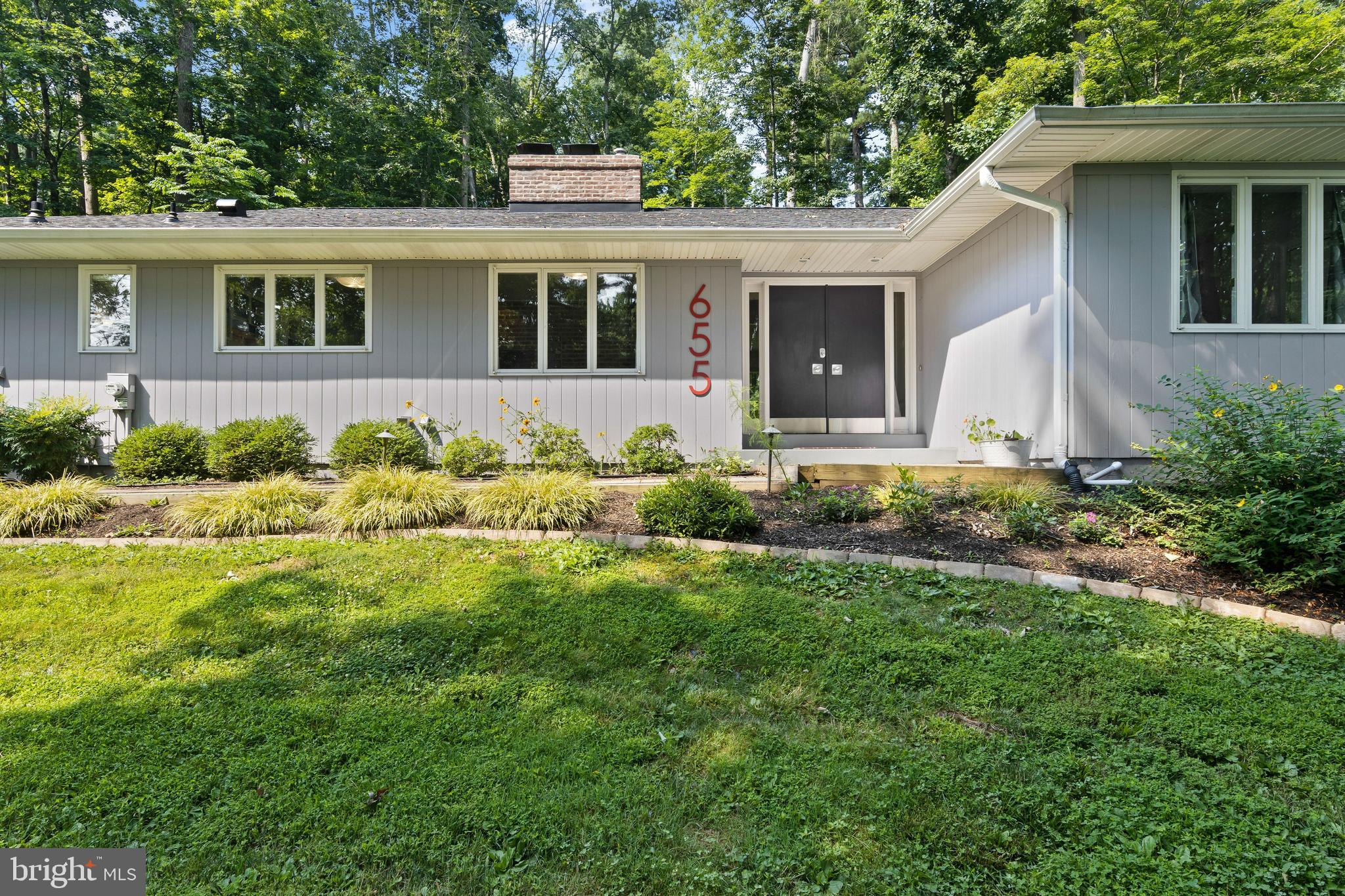 Classic mid-century modern style home in a great neighborhood in Radnor Township! This 3-4 BD, 2/1 BA ranch offers one-floor living, fresh paint, neutral décor, gleaming refinished wood floors, and expansive walls of windows which provide sweeping views. Trees were removed and trimmed so that this home is light and bright, yet the natural setting is still very private. Slate-tiled Entrance Hall opens to expansive Great Room with brick fireplace and ample space for dining, relaxing, and entertaining. The updated Kitchen features new stainless appliances, new granite counters, new subway tile backsplash, and new flooring. This area is also accented by a built-in brick grill. Enjoy casual family dining in the adjacent Breakfast Area which also opens to the Entrance Hall. Nearby is a Family Room/Study with built-ins that would also work well as a private Office, Playroom, Music Room, Exercise Room, or even a 4th Bedroom. This side of the home also has a main floor Laundry/Mudroom Area and indoor access to the oversized Garage. The bedroom wing is privately located on the opposite side of the house. The very large Master Bedroom has 2 closets (one walk-in) and wonderful views of the rear yard. The Master Bathroom has been completely renovated and features new fixtures, a wide vanity and large glass-enclosed shower. Two more Hall Bedrooms share a Hall Bath, which has new fixtures and a large new vanity as well. A Powder Room and several closets, including a very large walk-in closet in the bedroom wing (which could be used as a computer area) complete the main level. Downstairs is a large unfinished basement which offers ample space for recreation and storage, and great potential for finishing into additional living space. A 2nd set of stairs conveniently lead from the basement to the 2-car Garage. New roof (2018), new whole house generator (2017), new gas Heat and A/C (2020), new gas hot water heater (2018), and MANY other improvements. There is a patio area to the left 