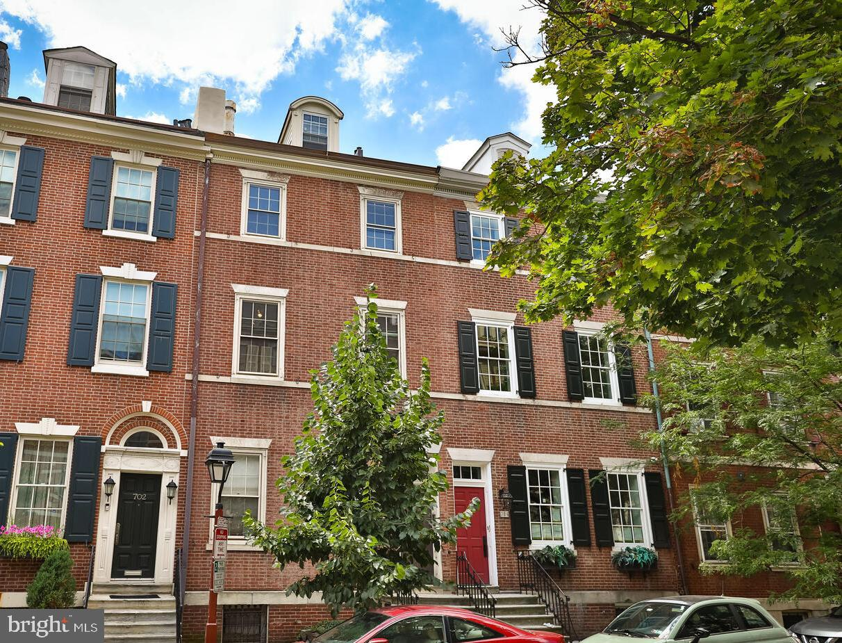 This enormous Federalist Society Hill townhome was built c.1810 and renovated, in 1972 with a distinctly mid-century Modern approach, by renowned Philadelphia artist Sam Maitin with the help of his brother Irving (AIA), an award-winning, Harvard- and Penn-educated architect. The Artist's studio still occupies the first floor and features a massive open space with 10-foot-high ceilings; the three floors above were the family residence.  A spacious eat-in kitchen at the rear of the second floor opens onto a large living area with fireplace and the front room which has a full en-suite bath and can serve as both family room and guest bed. The third floor has two well-proportioned bedrooms and shared bath, and the top floor has a primary bedroom suite with an anti-chamber/library/sitting room separated from the sleeping area by a 12-foot x 8-foot barn door. The house is looking for its next iteration from a buyer who wants to put their own imprimatur on this a distinctive and stately home on one of Society Hill's finest blocks. The first floor can remain a professional space or be transformed into the family living area, making room for more beds on the upper floors. With the included additional lot (703 Addison) that extends all the way back to Addison Street in the rear, there is ample room for 2-car parking along with a very generous garden area.